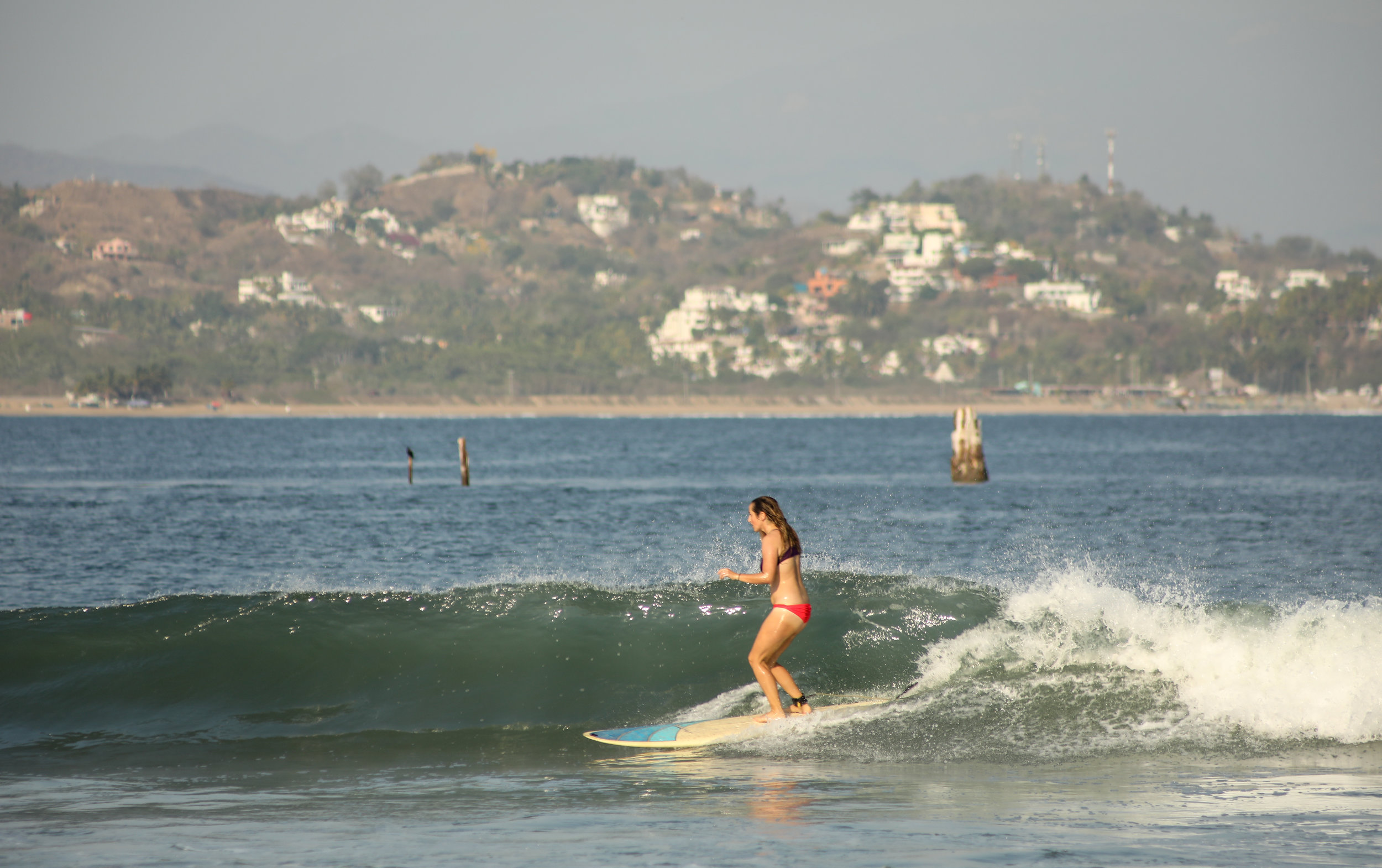 Carly Shredding with the wreck of San Luciano in the background.