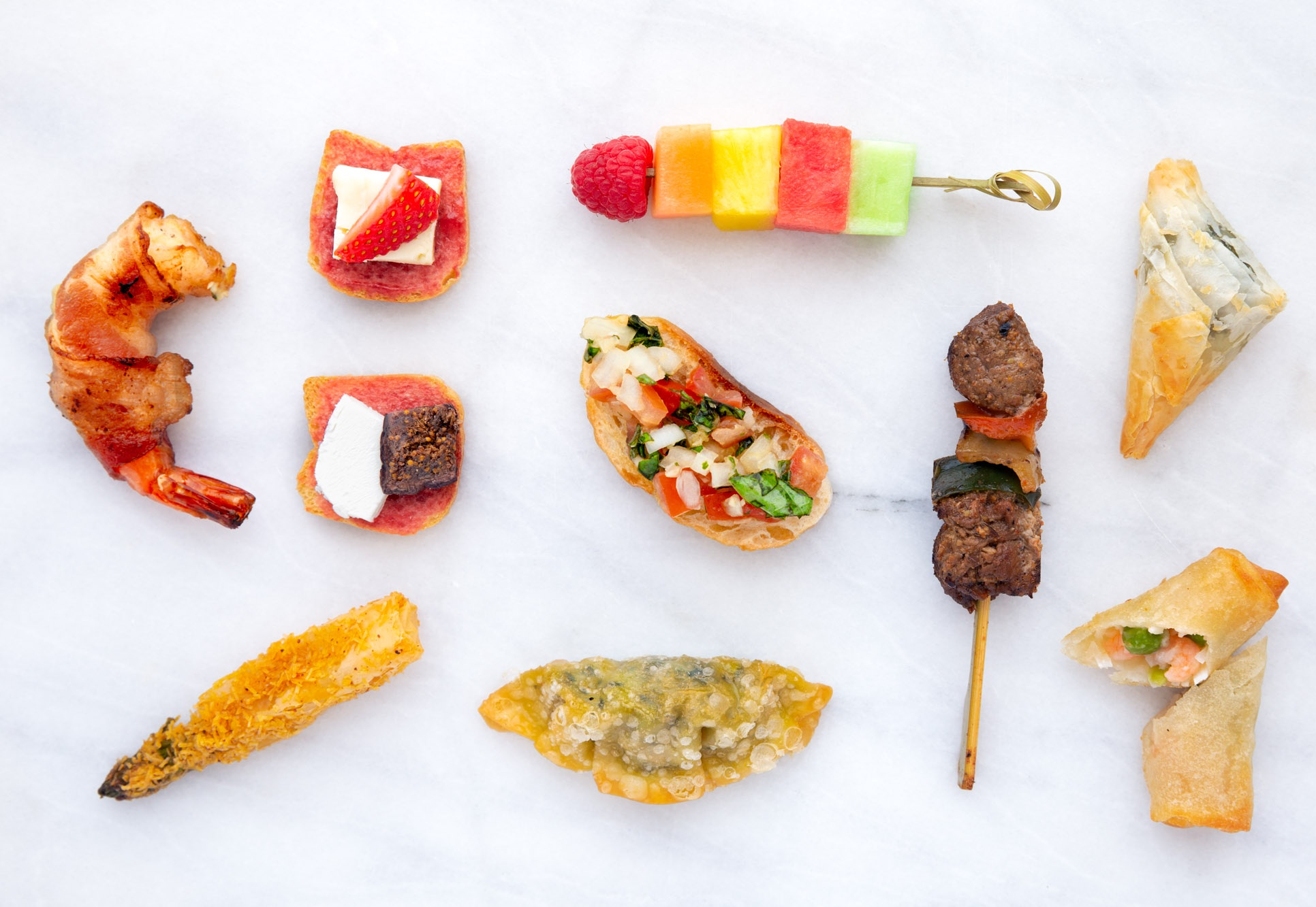 Top Row, L-R: Bacon Wrapped Shrimp, Brie & Strawberries on Toast, Seasonal fruit Skewer, Spanakopita; middle Row, L-R: Fig & Goat Cheese on Toast, Bruschetta, Chipotle Churrasco Steak Skewer; Bottom Row, L-R: Asparagus Asiago Roll, Kale Pot Sticker, Thai Shrimp & coconut Spring Roll; PC,  Taming of the Spoon