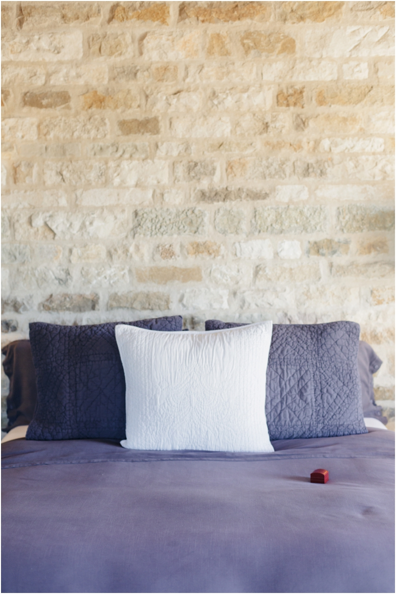 red ring box on purple dressed bed in front of stone wall