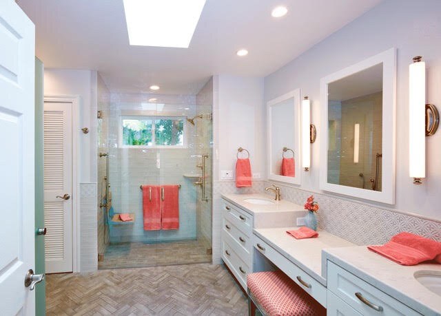 Plenty of both artificial lighting and natural lighting are provided using recessed cans, vanity sconces, windows and a skylight.  The tile floor is laid in a herringbone pattern throughout the bath in a slip resistant porcelain. As it moves into the shower the pattern becomes staggered so that the slope to the drain is maintained and there is no dam or threshold for the client to step over.