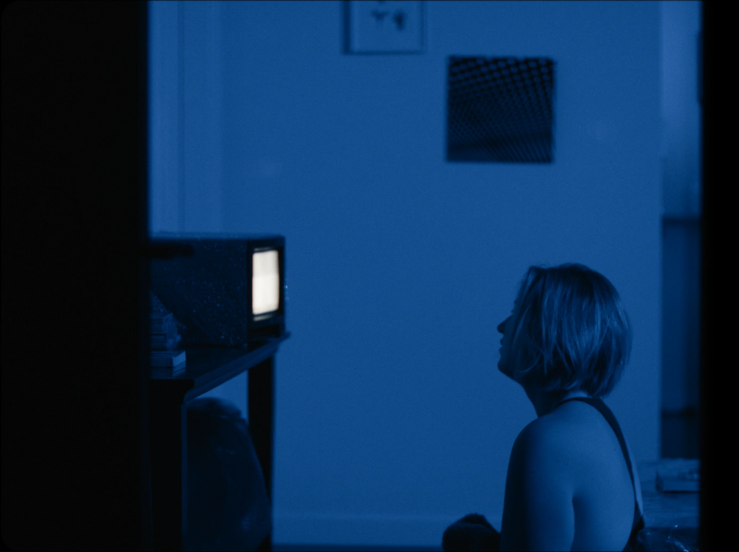 Still from  Watching Us  (2018) where a woman stares at a white TV screen while sitting in a monotone blue room.