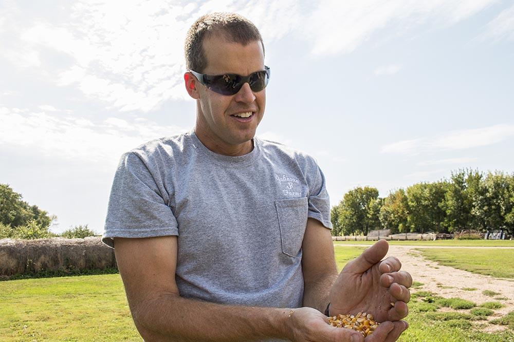 Aaron Johnson holds a handful of corn at his farm in Madison, South Dakota, Johnson Organic Farm.