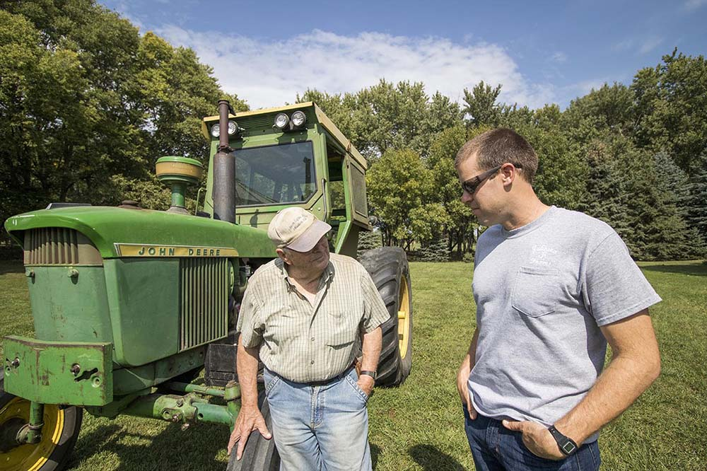 Aaron and his father, William, stand in front of their tractor.