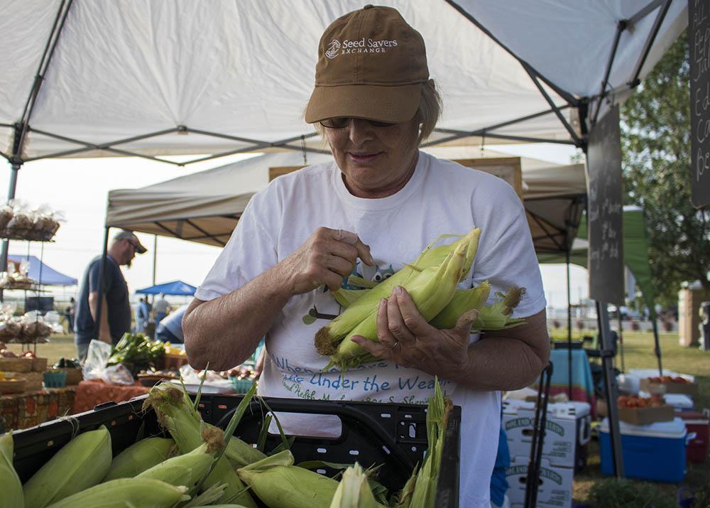 Rachel gathers corn for a customer at Landon's Greenhouse Saturday Farmers Market in Sheridan, Wyoming.