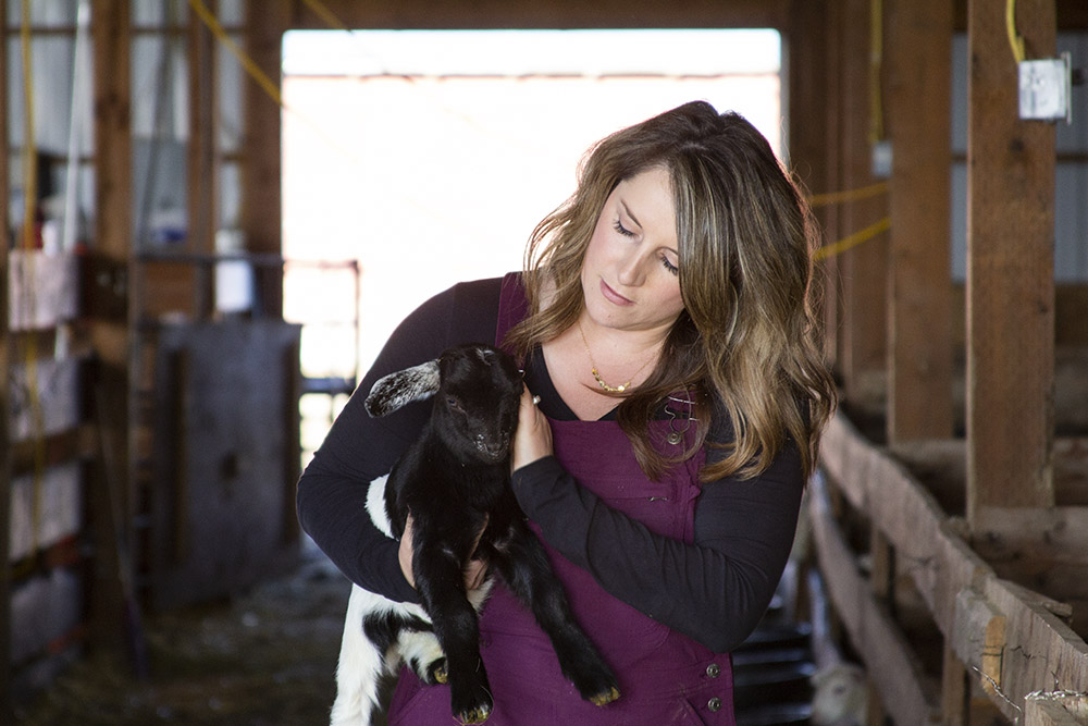 Sara holding a goat in the barn.
