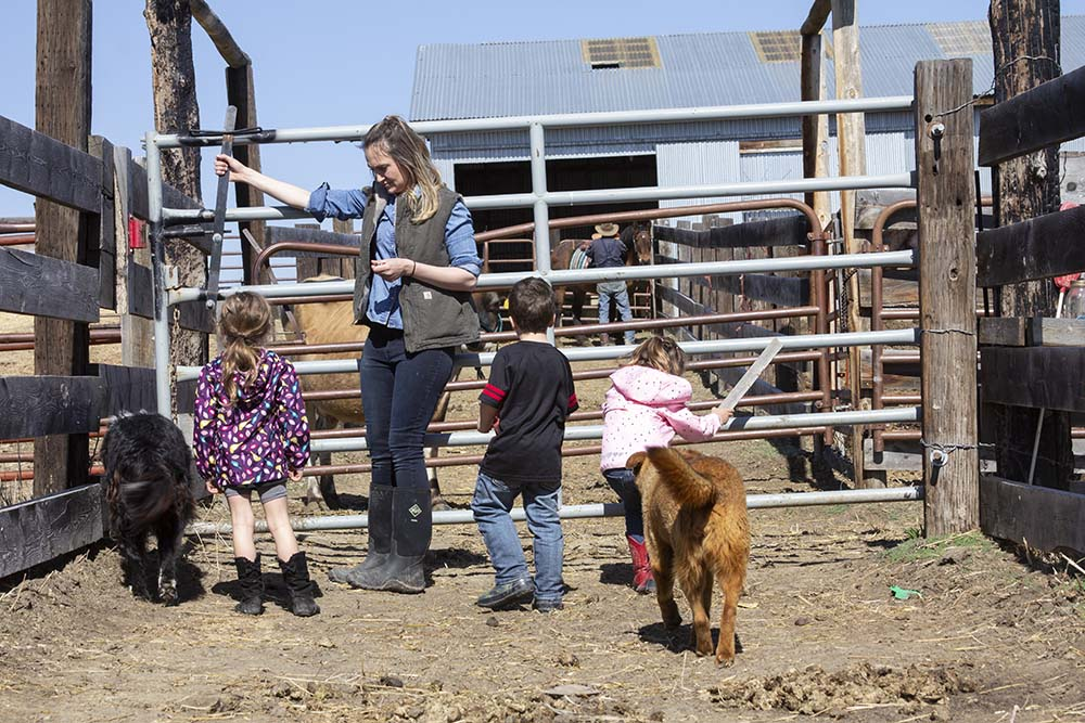 Annika opens the gate for her niece Delilah (left), nephew Drake, and daughter Stevie (far right).
