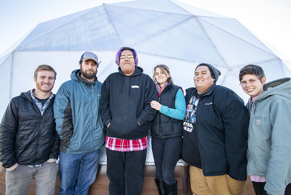 From left to right, the Sicangu Food Sovereignty Initiative Staff, Aaron Mandell, Mike Prate, Edwin Her Many Horses, Rachel Kent, Matt Wilson and Hollis Vanderlinden in front of a greenhouse at the Keya Wakpala Garden, in South Central South Dakota, on the Rosebud Reservation.