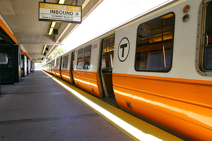 Image of Orange Line train stopped at a station platform.