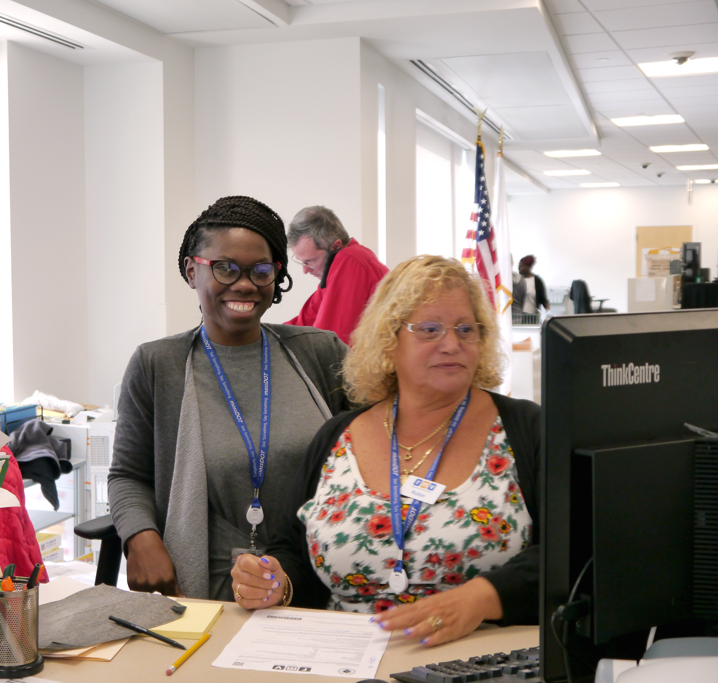 Image of two customer service representatives at the Haymarket Service Center working as a team to complete a transaction.
