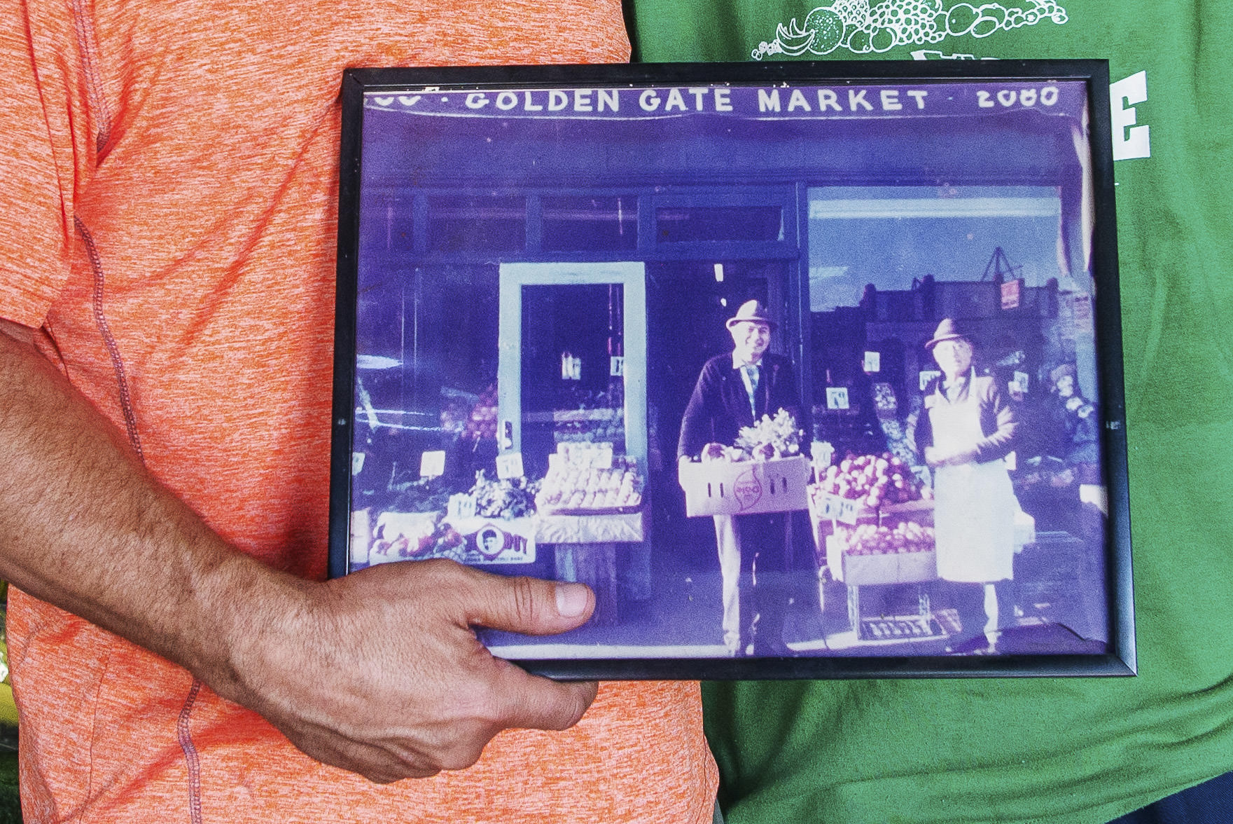 GoldenGates grocer on Flatbush Avenue. Owner with son holding up photo f grocery when owned by grandfather