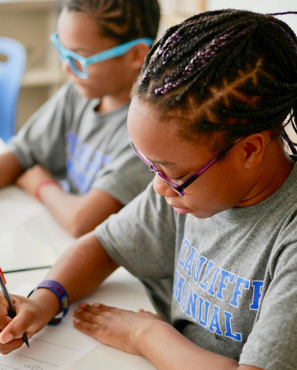 Two girls wearing glasses writing