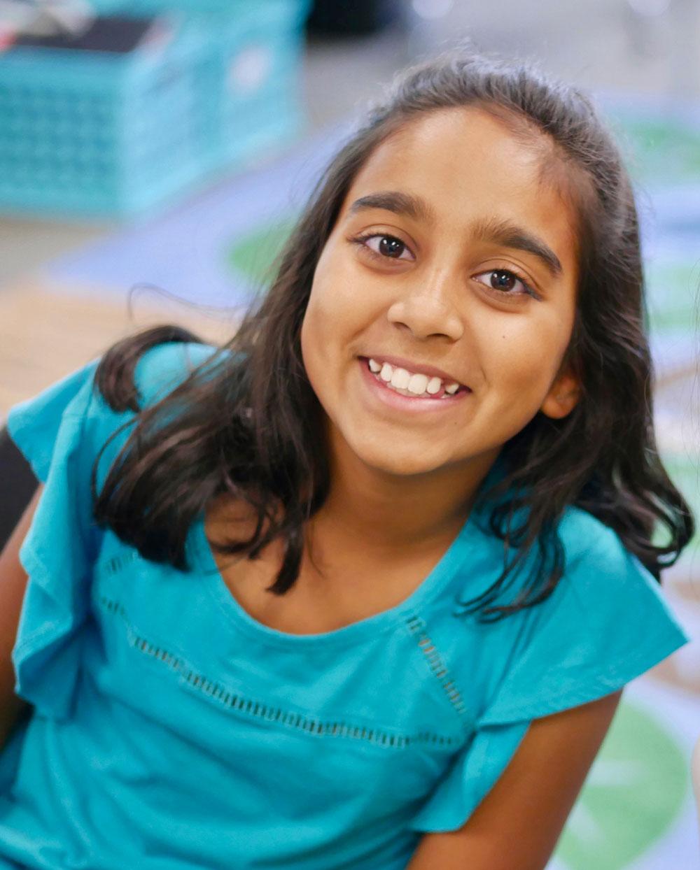 Smiling girl wearing turquoise shirt