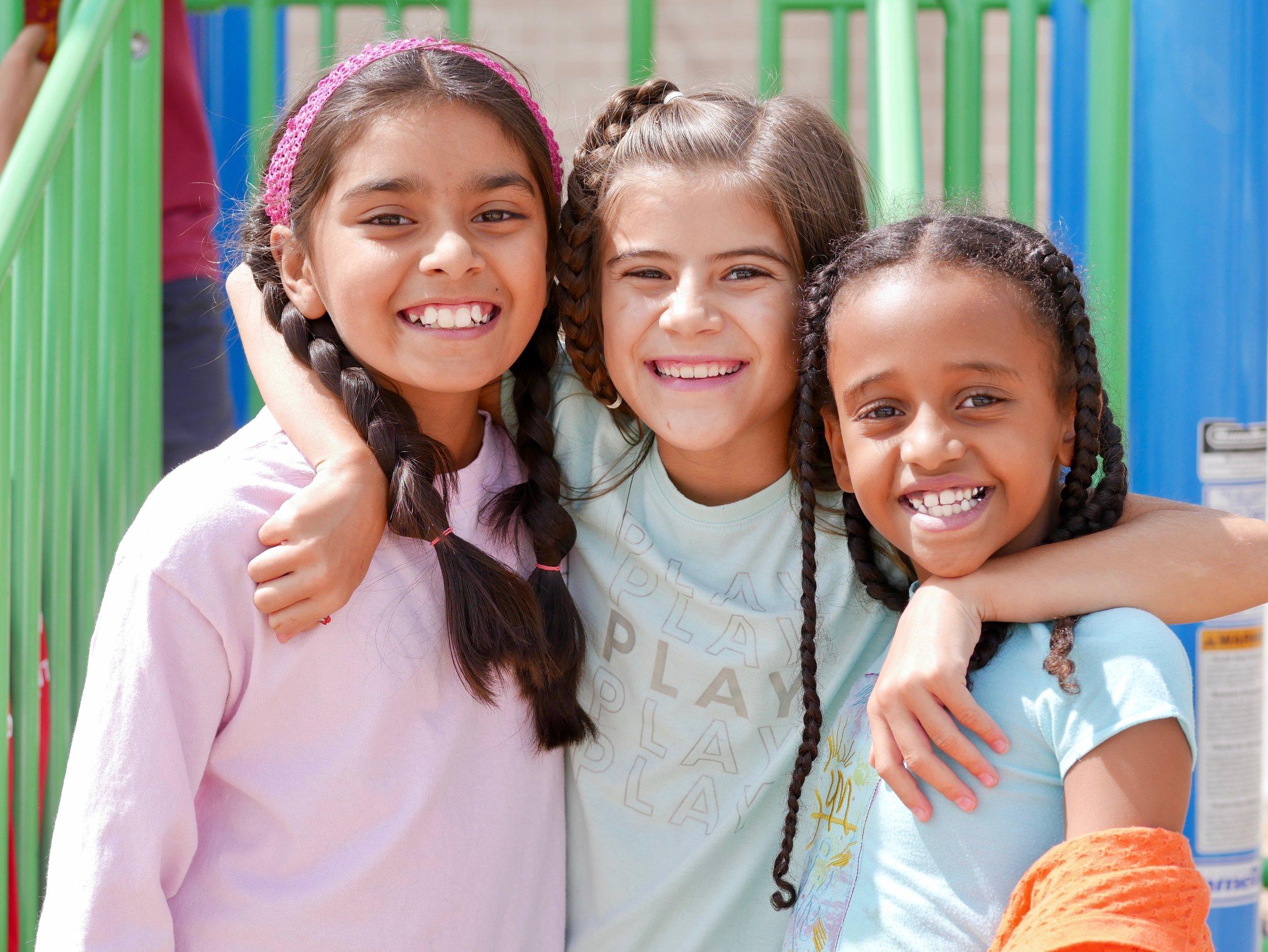 Three smiling girls at playground