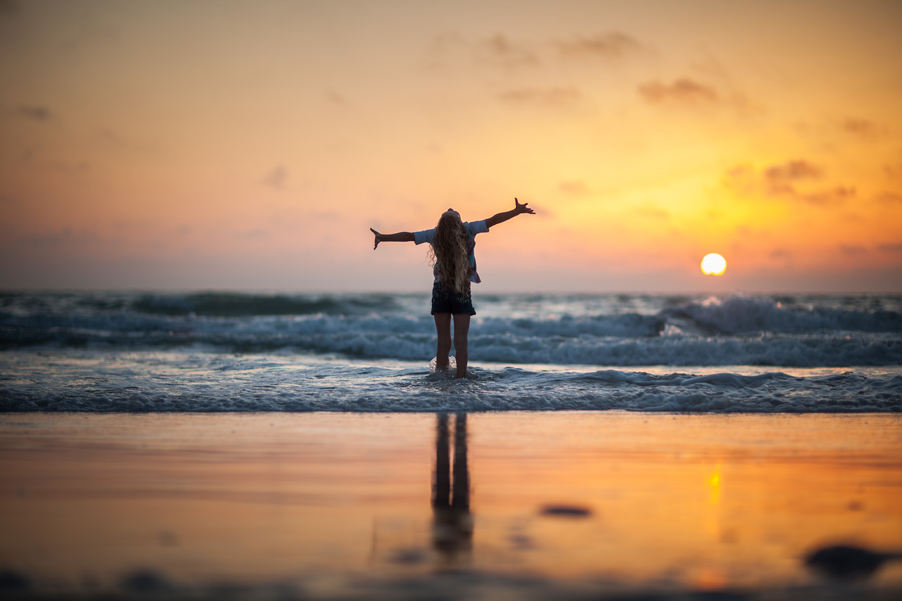 Woman-Standing-Ocean-Shore-Arms-Air-Enjoying-Sunset-X2.jpg