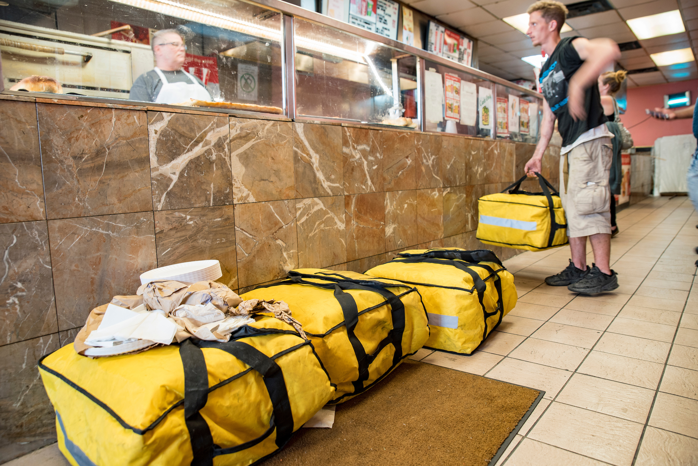 A PMA Bike Ride volunteer picks up one of many carry-bags of pizza from Four Sons Pizza in Kensington, Philadelphia.