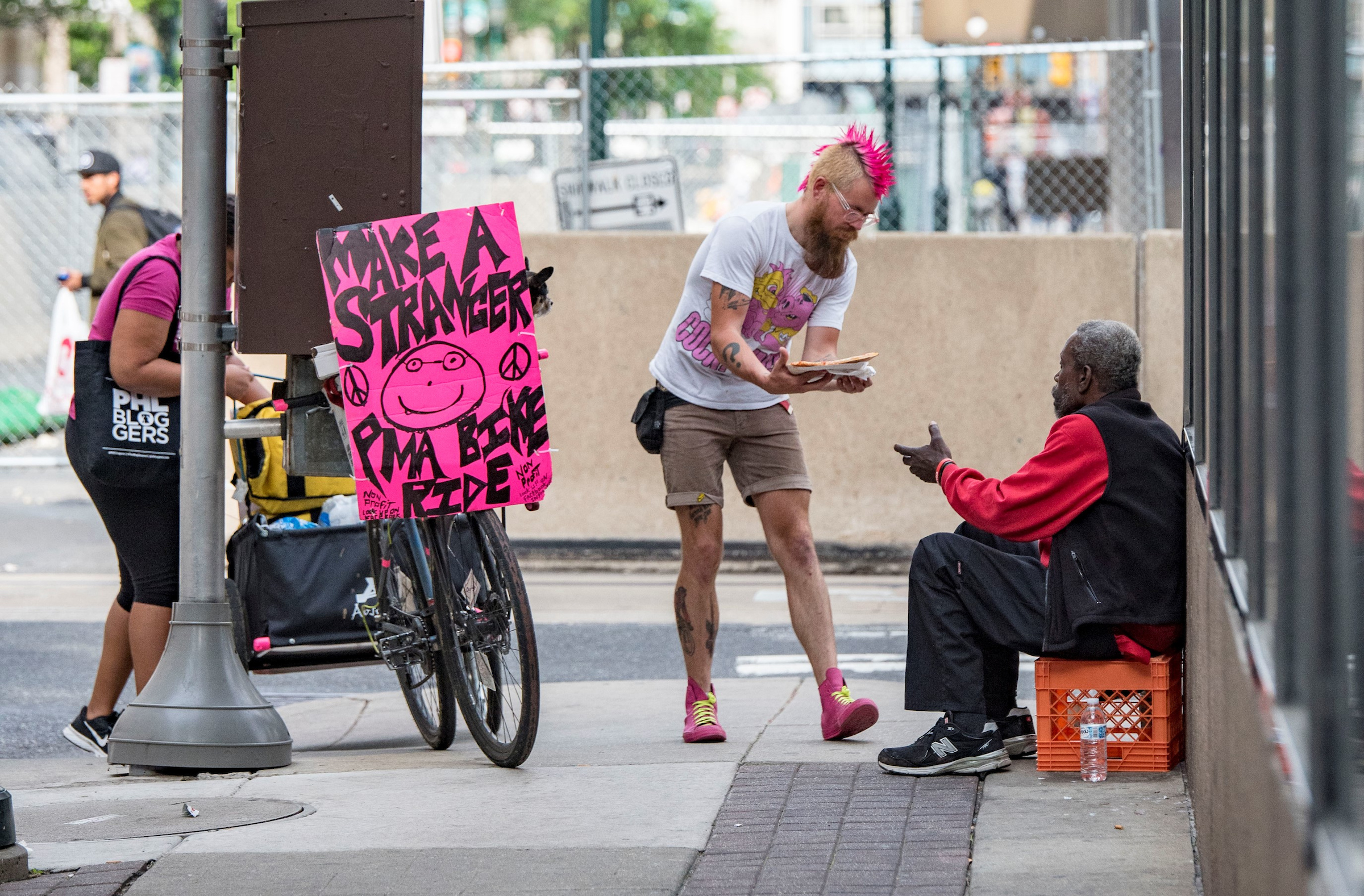 """Joe shares pizza with a man in Philadelphia's center city. He is famous for his pink mohawk and neon signs calling on people to """"Make a Stranger Smile""""."""