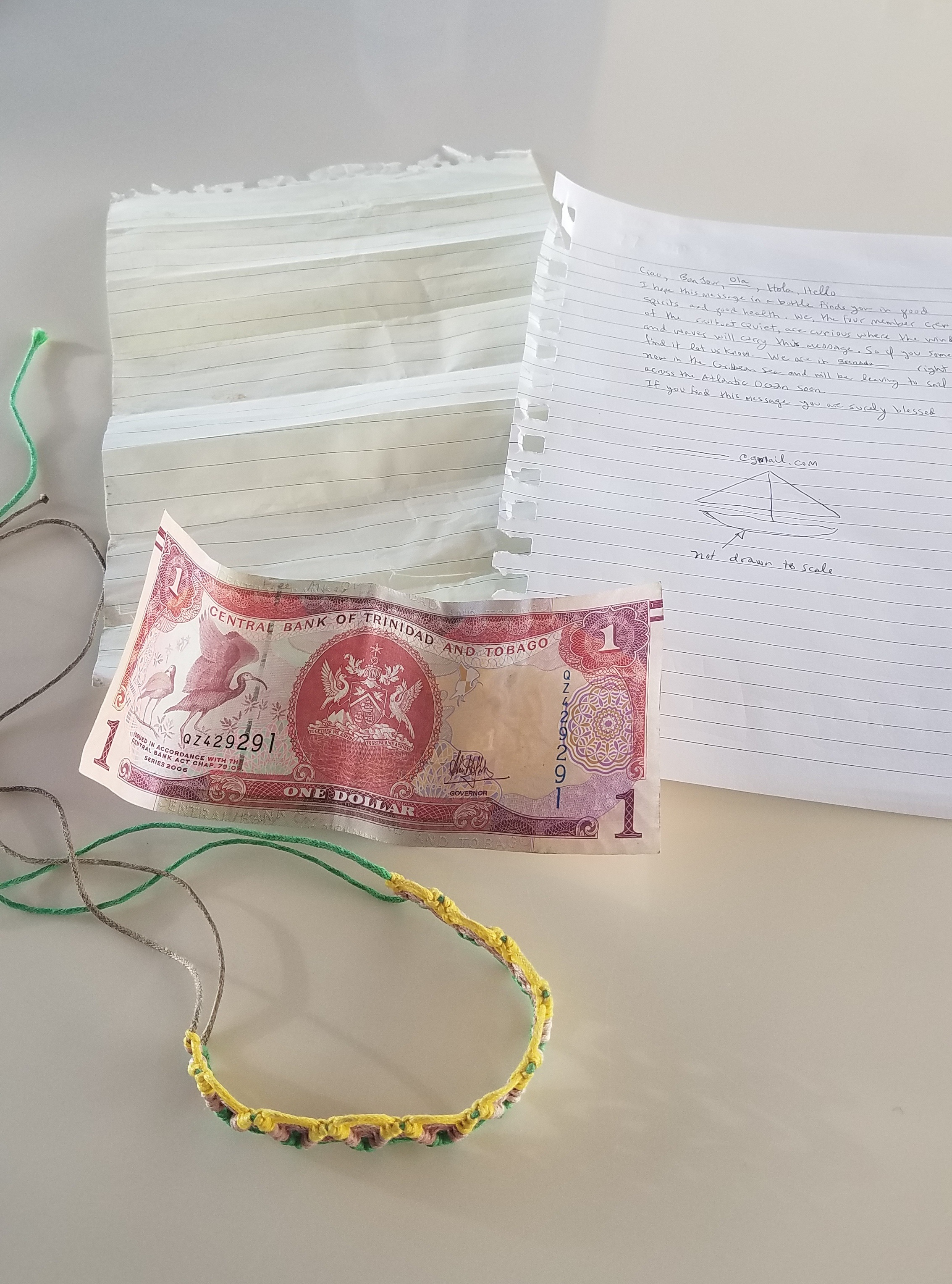 The contents of the bottle; the original faded note, the reconstructed version of the note, the dollar from Trinidad & Tobago and the bracelet