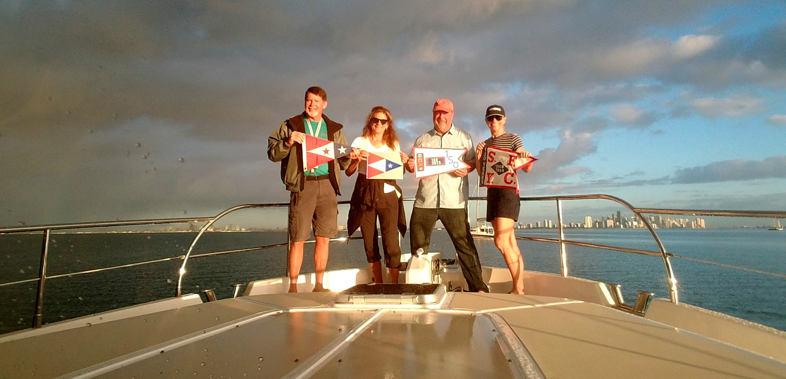 The 'Burgee Brigade' on the deck of The Independence in front of the Miami skyline, Biscayne Bay, FL. Larry holds the SFYC burgee, Kappy - the 150 Anniversary Book, Mark - our 150 year anniversary burgee & Jamie - the 120 year anniversary burgee