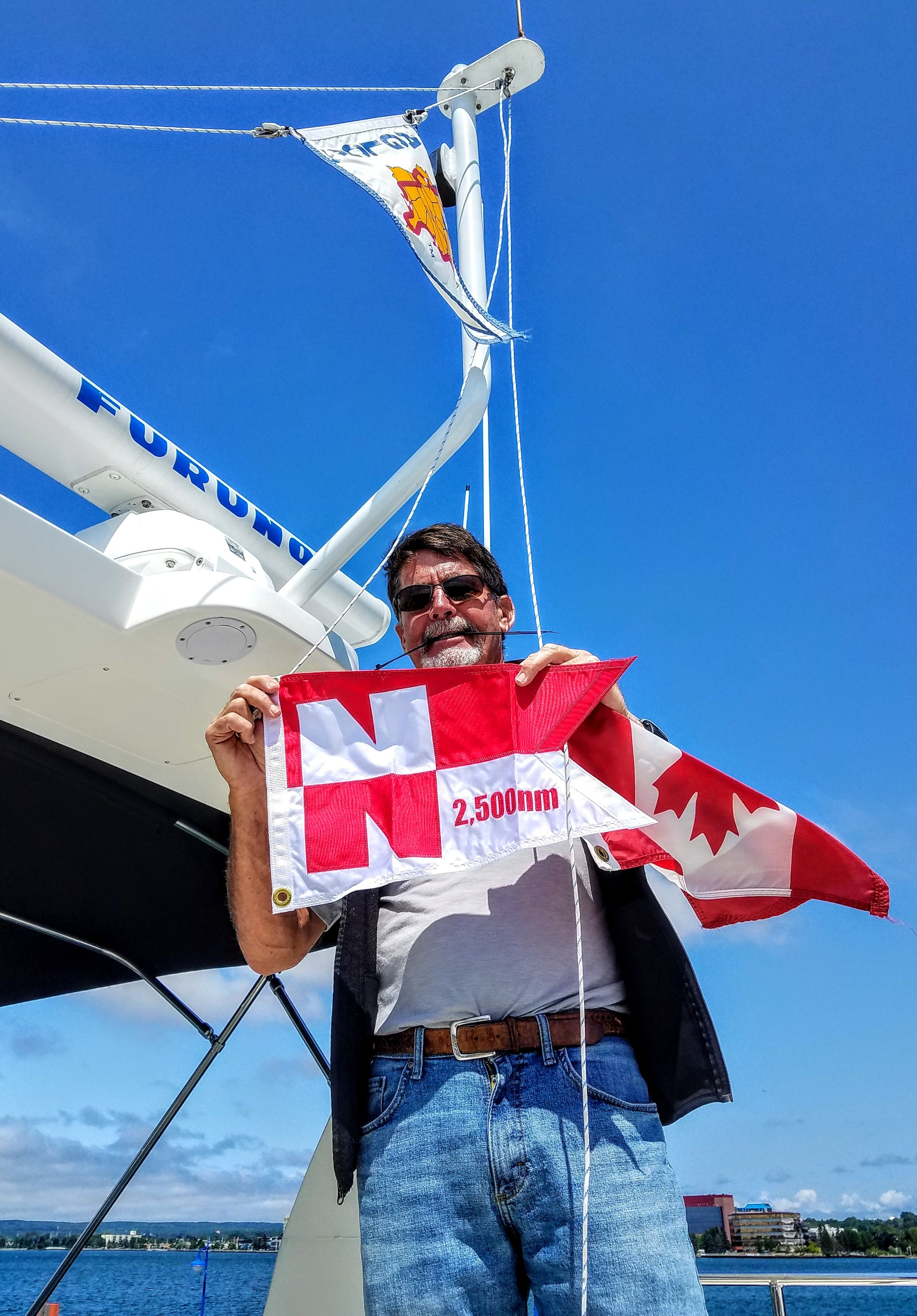 Larry replaced our Canadian courtesy flag with our Nordhavn 2,500 nautical mile pennant flag after re-entering the U.S. at Sault Ste. Marie, MI in the George Kemp marina.
