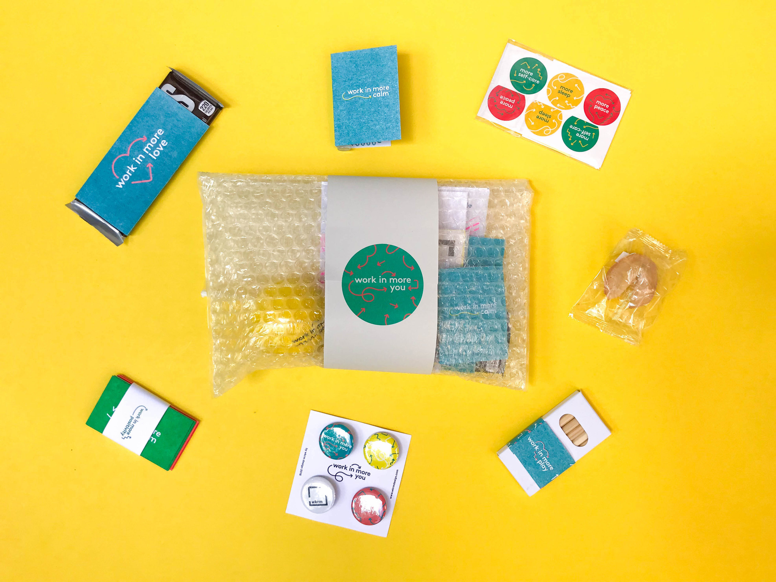 All the products included in the work in more you kit.  What's included: Chocolate, essential oils, stickers, motivational cards, buttons, coloring pencils, a coloring book, fortune cookie containing random motivational messages, soothing tea, and a stress ball.