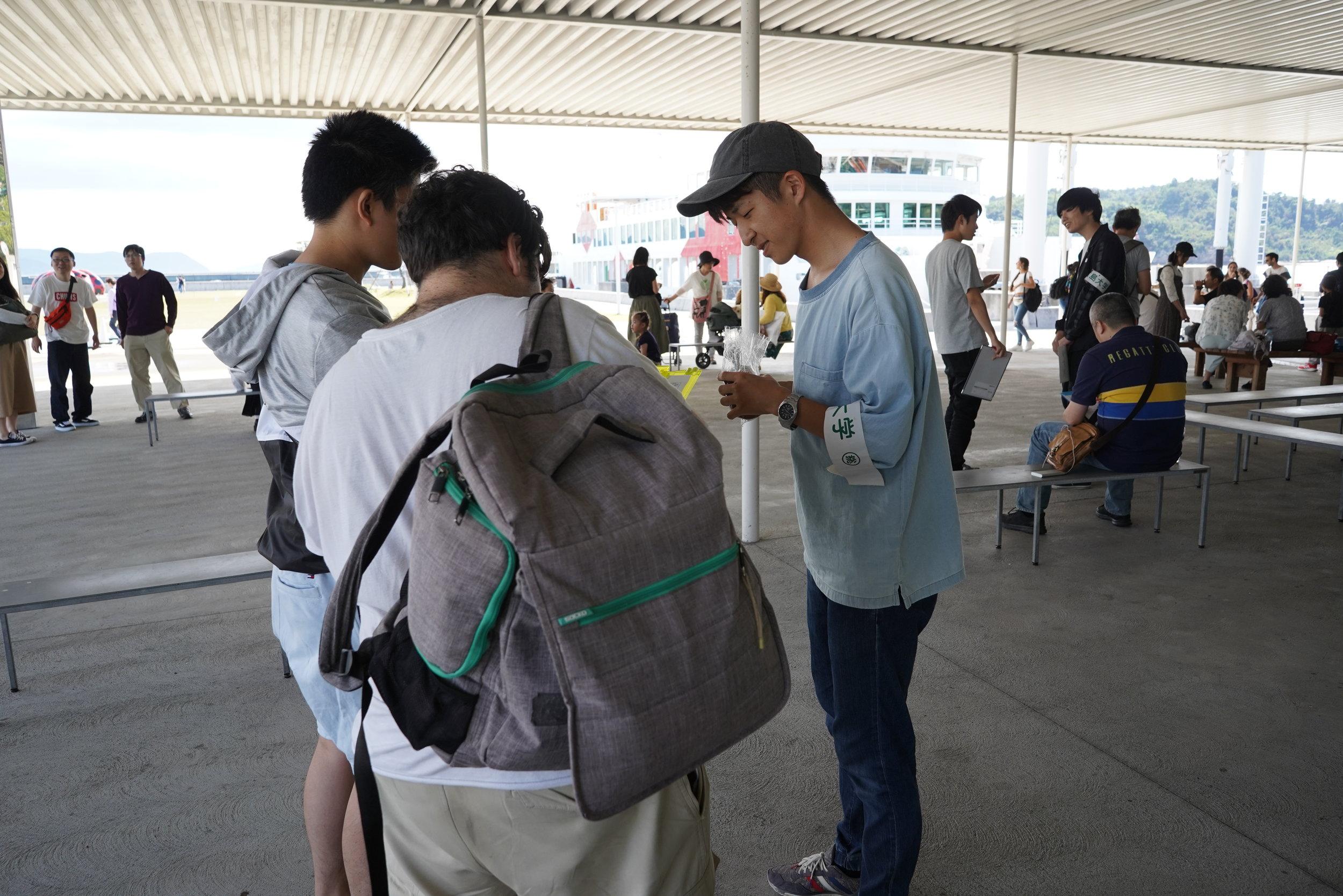 宮浦港では、学生たちが日本語、英語、中国語のアンケートで200人以上の観光客を調査しました。 At Miyanoura Port, students surveyed over 200 departing tourists with questionnaires in Japanese, English, and Chinese.