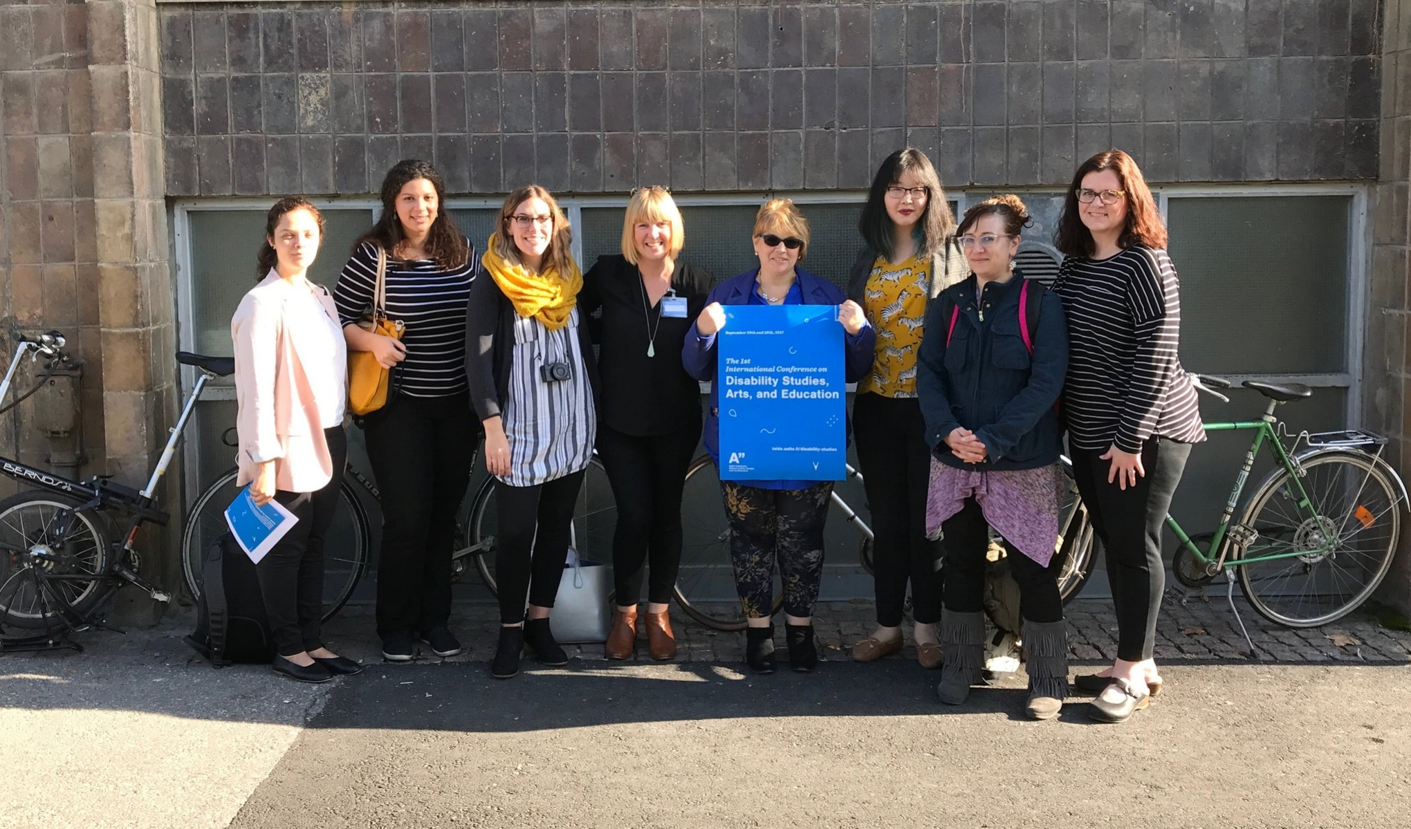 Eight members of Moore College of Art & Design Holding a blue poster from the 2017 First International DSAE Conference in Helsinki, Finland.