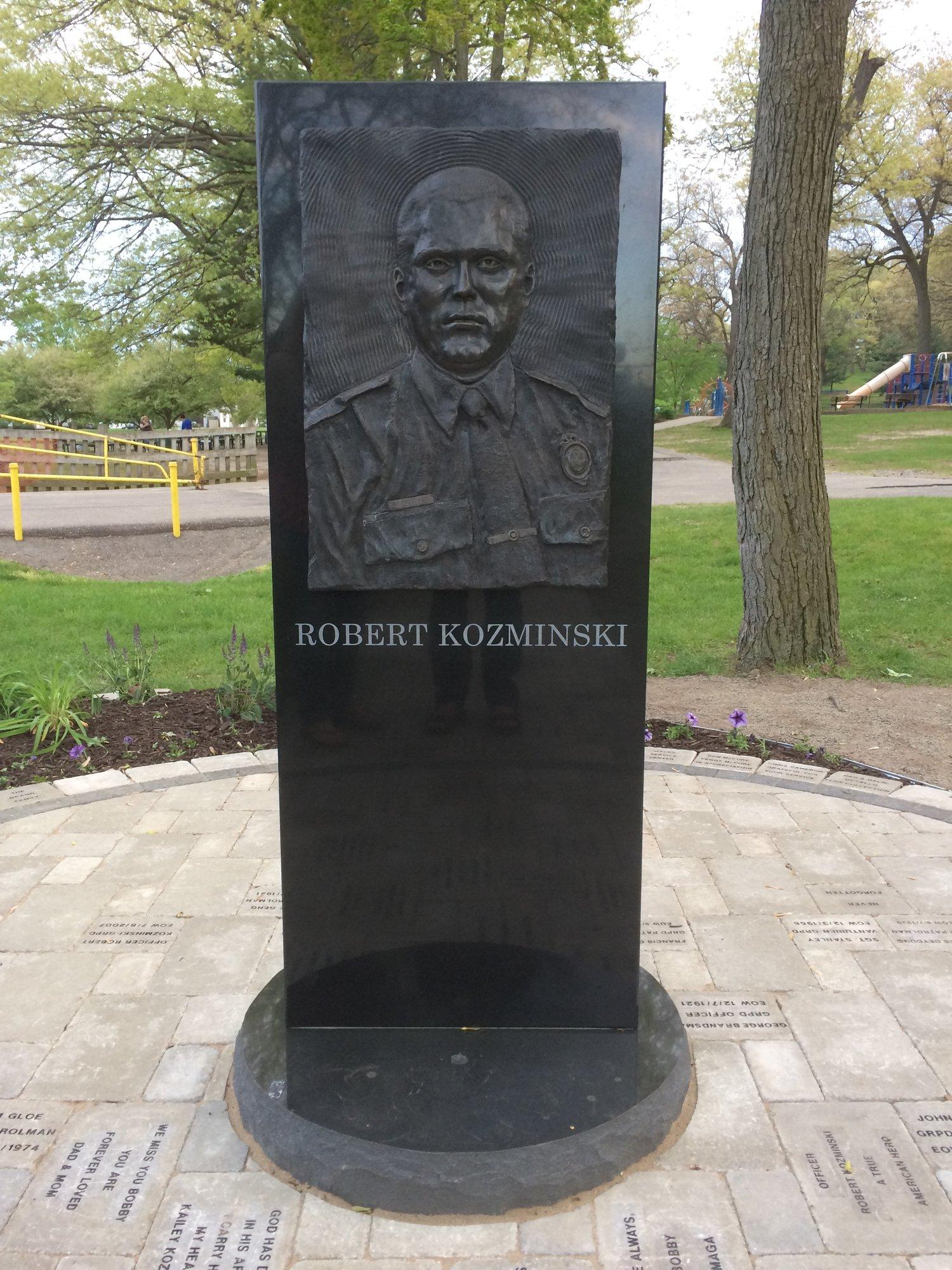 "Bronze relief memorial of fallen police officer ""Robert Kozminski"" is located at Richmond Park, 1101 Richmond St NW, Grand Rapids."