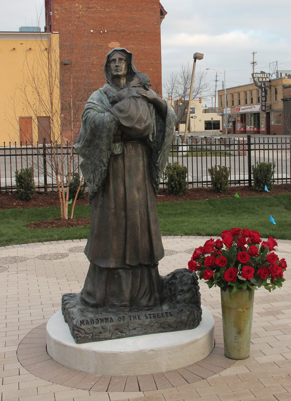 """""""Madonna of the Streets"""" his first bronze is located at 659 Bridge Street in Grand Rapids, next door to HELP Pregnancy Crisis Aid. The bronze is surrounded by the 20 mysteries of the Rosary in a relaxing green space."""