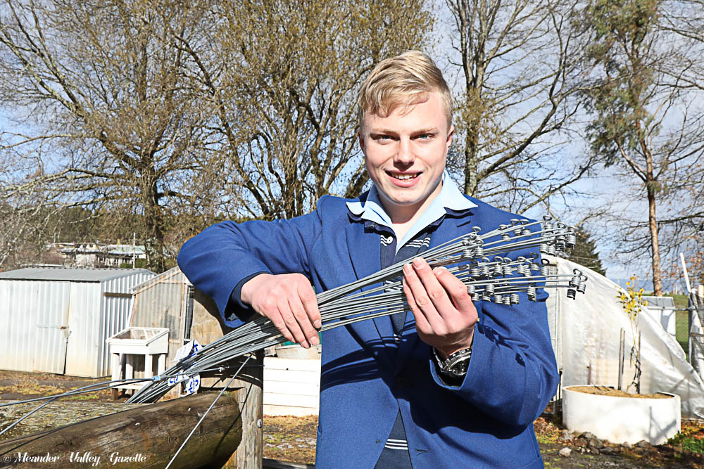 Deloraine High School student, 16 year-old Jayden Lee, pictured with his 'tie os' designed to make rural fencing quicker and easier.
