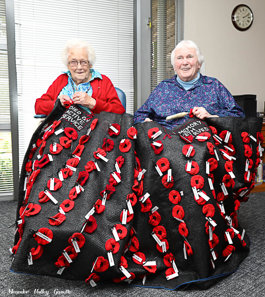 L-R Faye Woods and Bessie Westwood put the finishing touches on the impressive poppy banner. Photo by Mike Moores