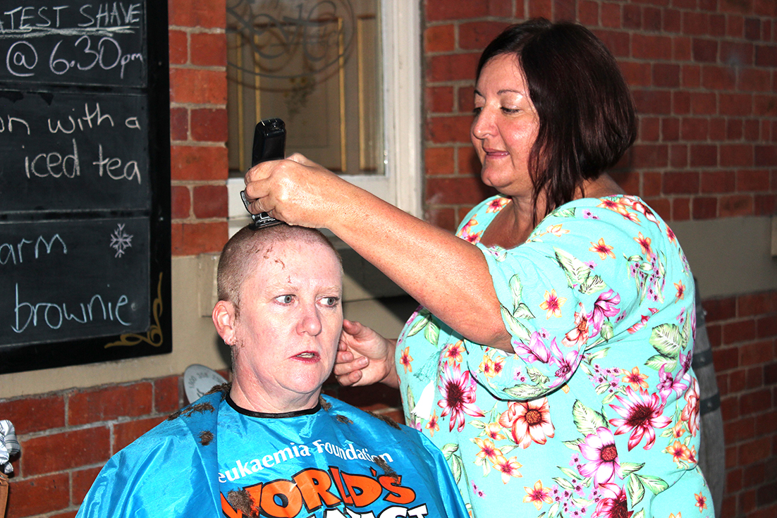 Outside the Empire Hotel for the 21st World's Greatest Shave, hairdresser Liz Walker wields her clippers on Mole Creek cave guide Angela Enright.   Photo | Hayley Manning