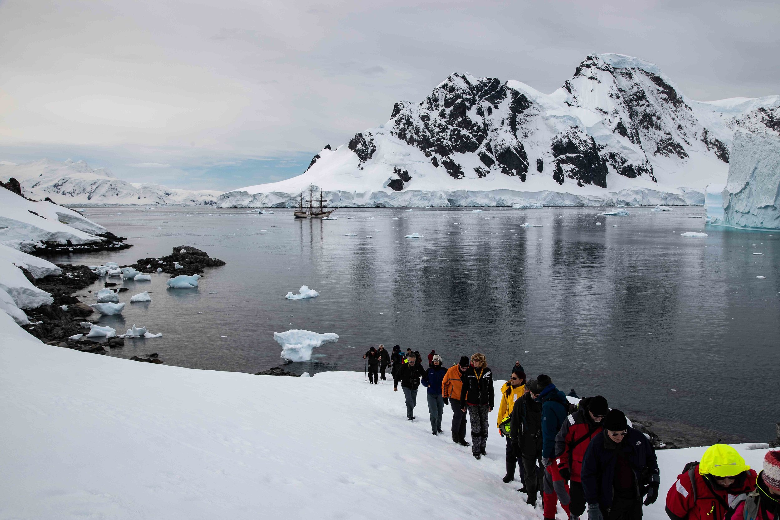 Europa  appears dwarfed by the landscape as the voyage crew take ahike at Orne Harbor to visit a chinstrap penguin colony.