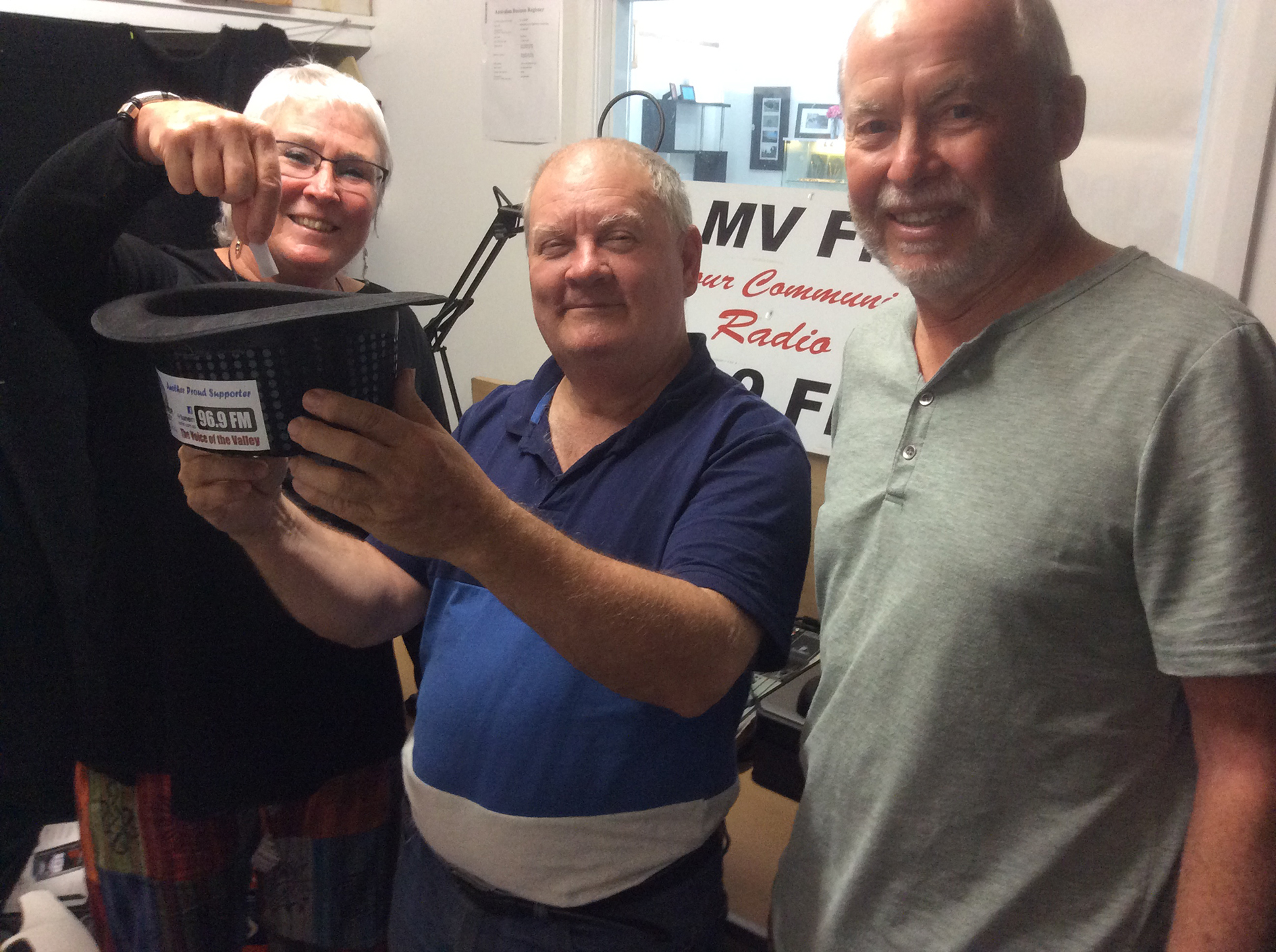 From left, Secretary Rijke McGough, Studio Manager / Vice President John Kenzie and Treasurer Tim Biggs picking a lucky winner out of the hat in the fortnightly Members' draw at the radio station.  Photo supplied