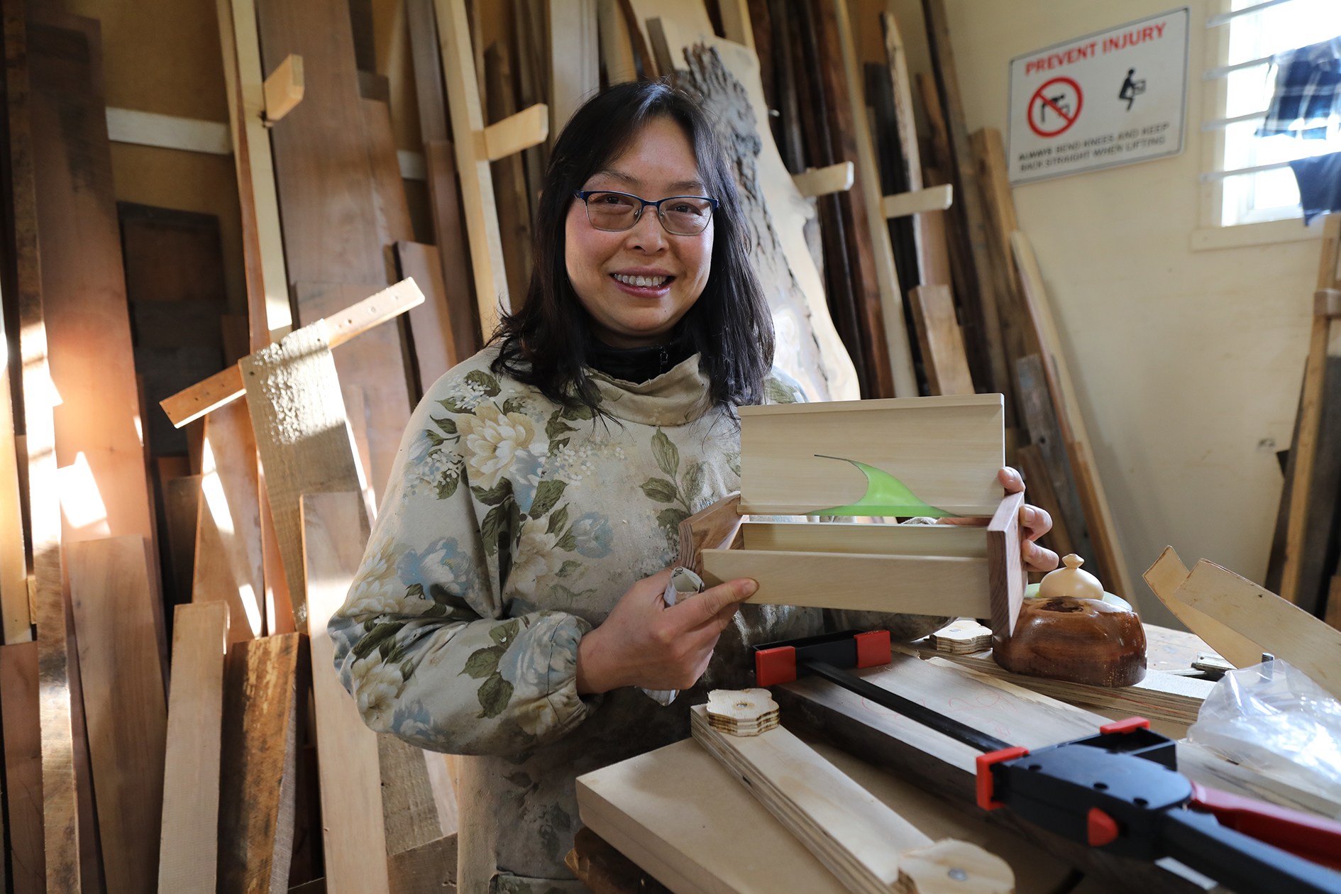 Hong Ma, at the Deloraine Community shed, with one of her newest creations, a small wooden box inset with translucent green resin.  Photo by Mike Moores