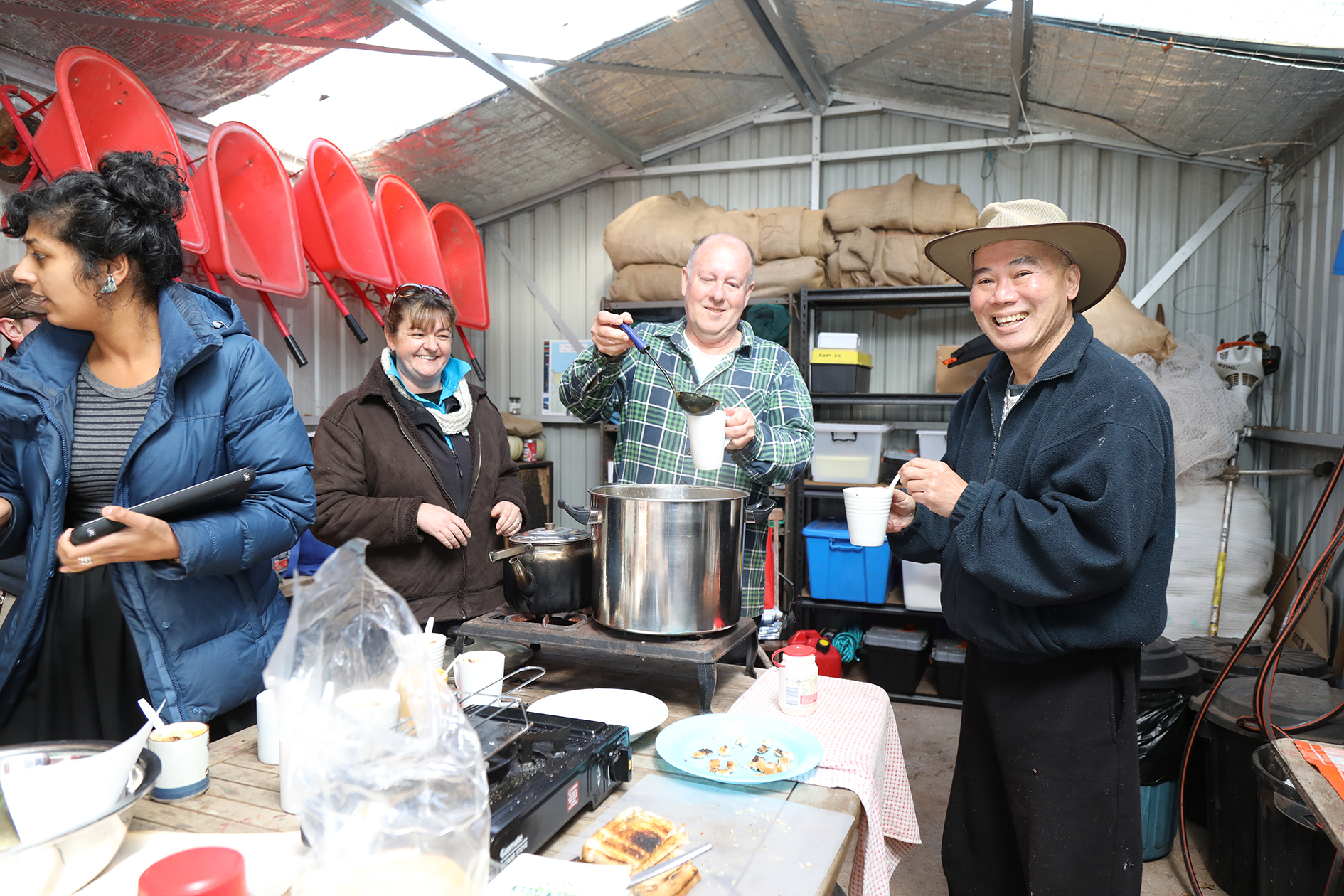 From left, Tanya King, David Hudson and Howard Hor sampling soup at the community garden.  Photo by Mike Moores