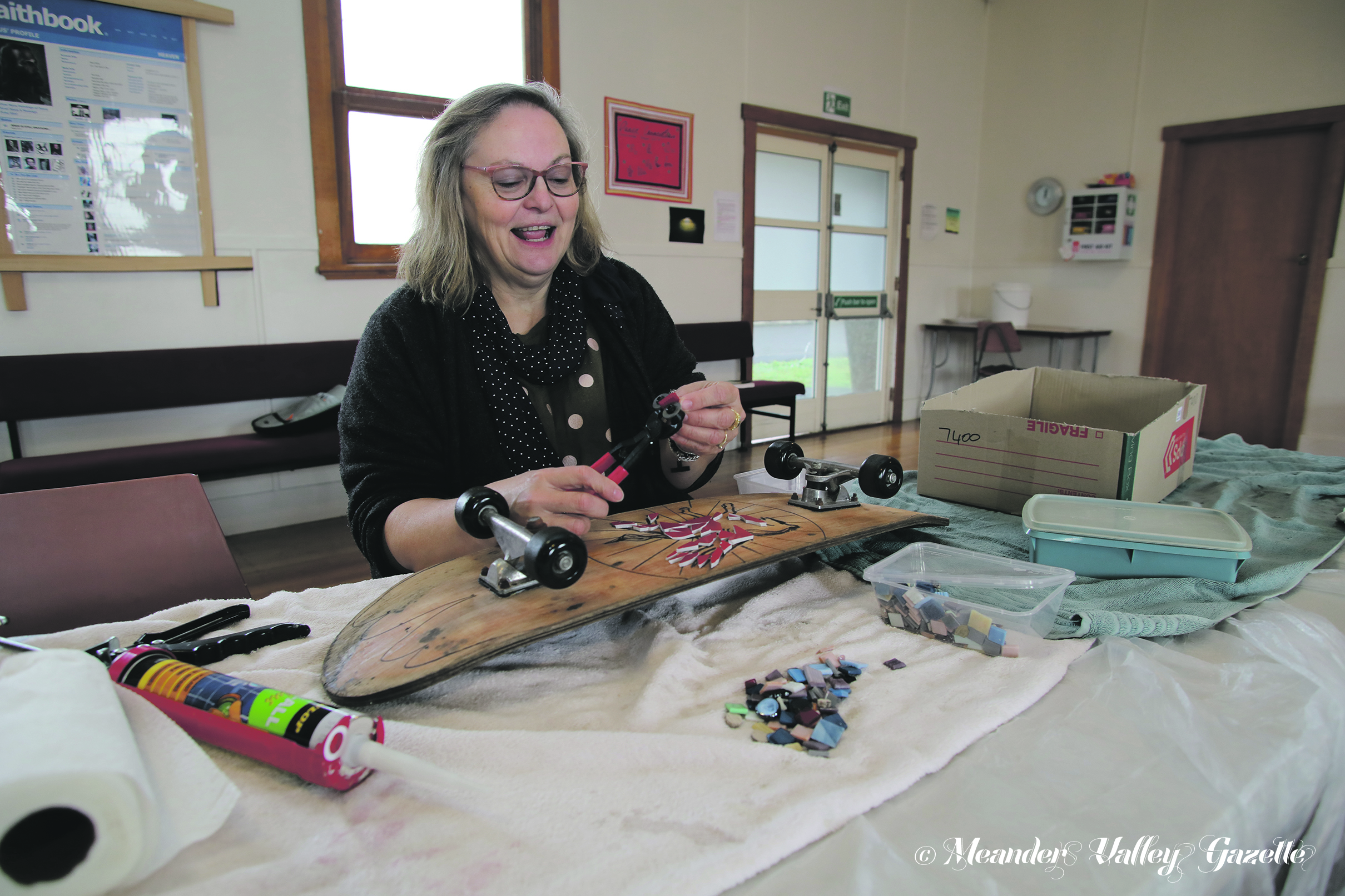 MVU3A member Susanne Puccetti works some of her mosaic magic on an old skateboard.  Photo by Mike Moores