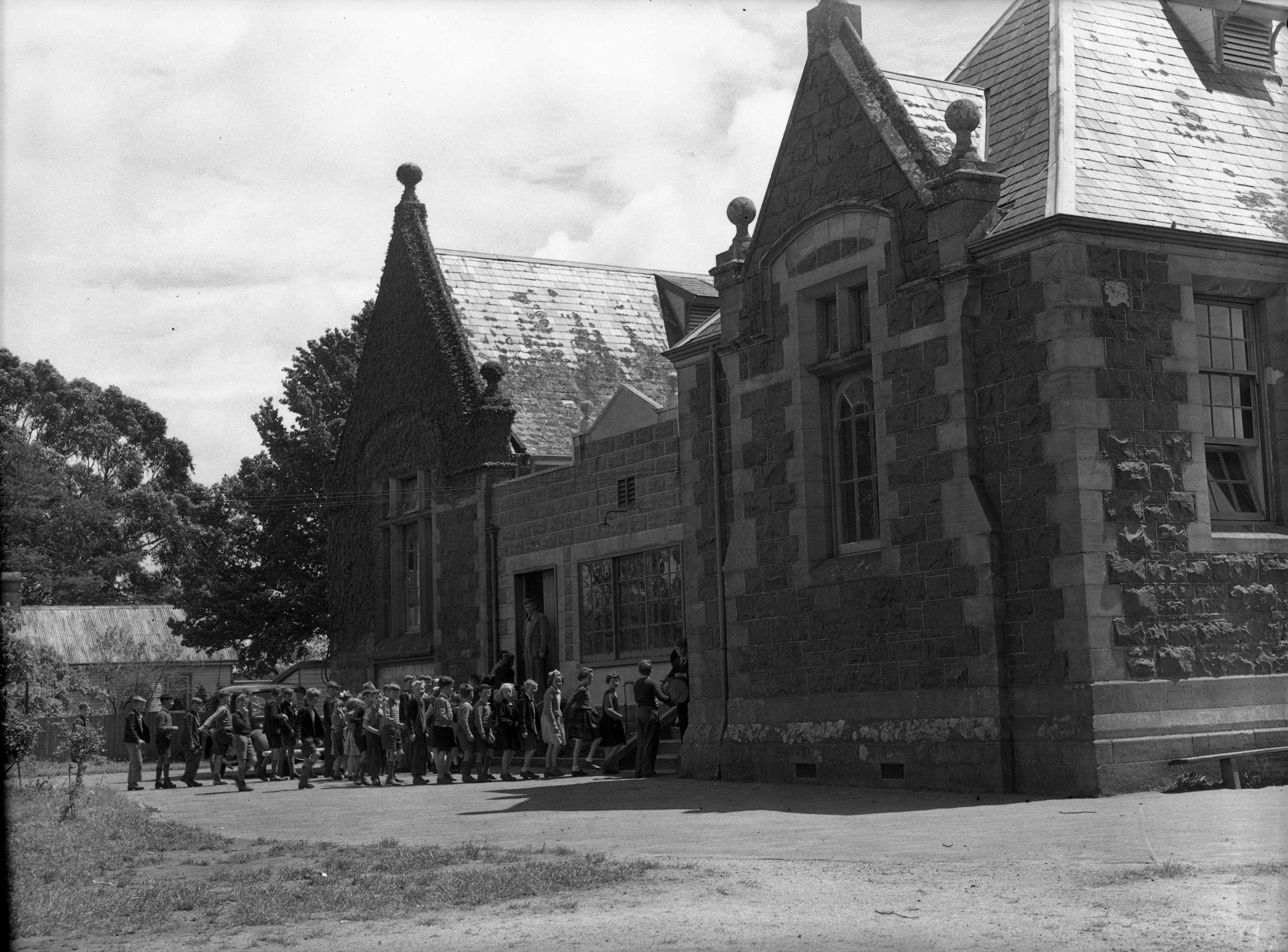 Westbury children line up to go inside the impressive bluestone building that once housed Westbury State School. Tasmanian archives: Westbury State School (1953).  Photo supplied