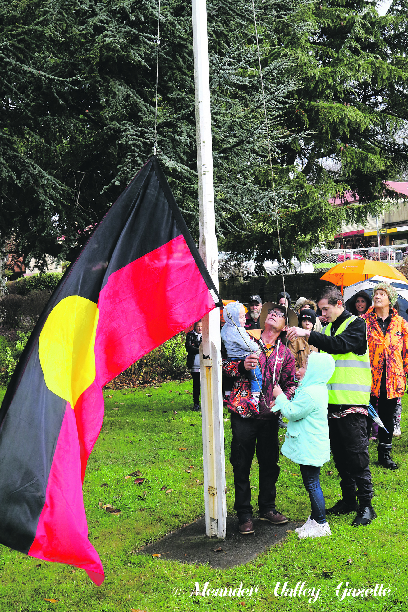 Cold and rainy weather for Deloraine did not put off attendees from celebrating at this year's NAIDOC Week ceremony. Deloraine Elder Hank Horton holds baby Layken West while helping to raise the flag .  Photo by Mike Moores
