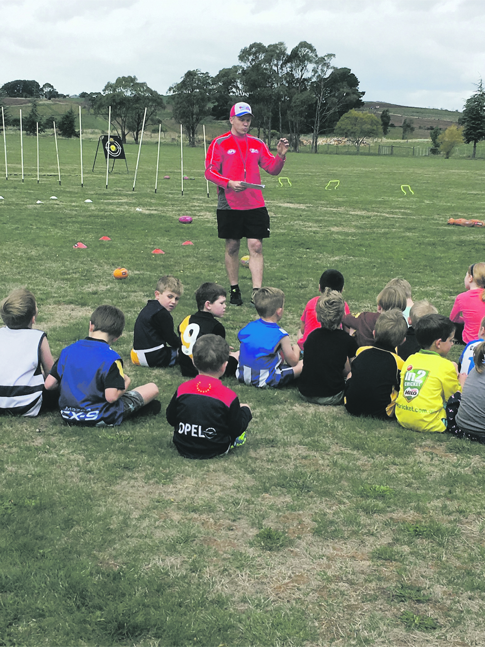 Photo Supplied  James Baldock at Auskick, with some possible future players for the Deloraine Roos or the Tasmanian AFL team.