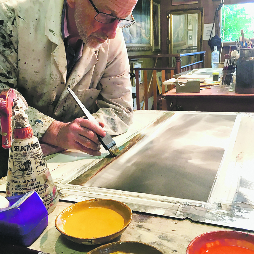 Photo supplied  Tony Smibert working in his watercolour studio.