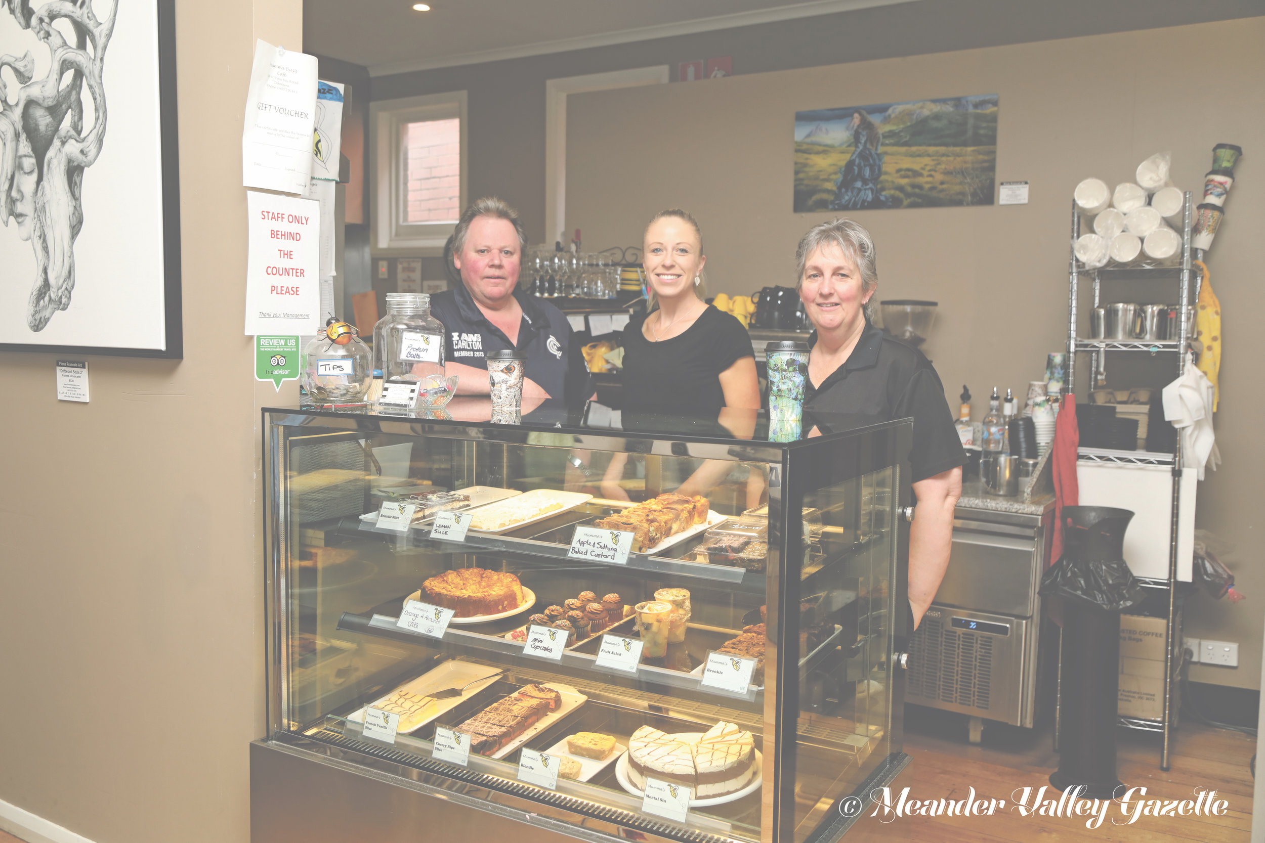 Photo by Mike Moores  Buffy, Natalie Woolford and Carolyn Bussey behind their fabulous cake cabinet at Mumma Buzz Café.