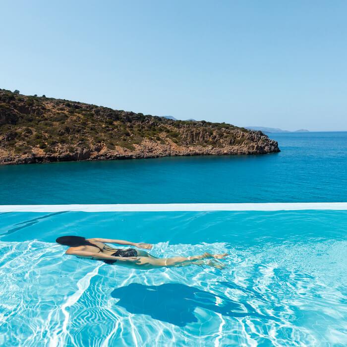 Daios-Cove-beach-blue-sea-women-swimming-under-water-pool-the-ghost-group.jpg