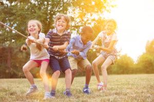 Multikulturelle Gruppe Kinder beim Tauziehen als Team in der Natur