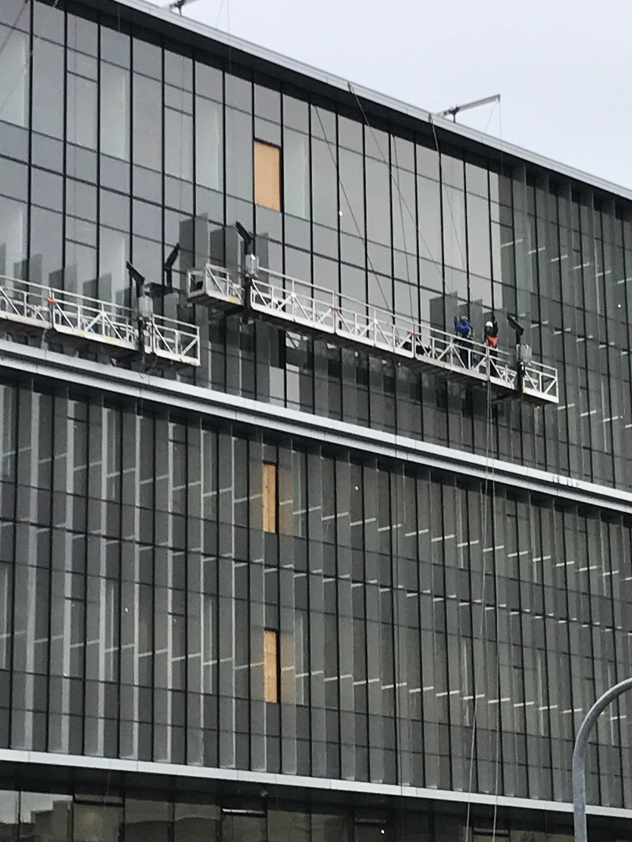 Glass solar fin installation in progress