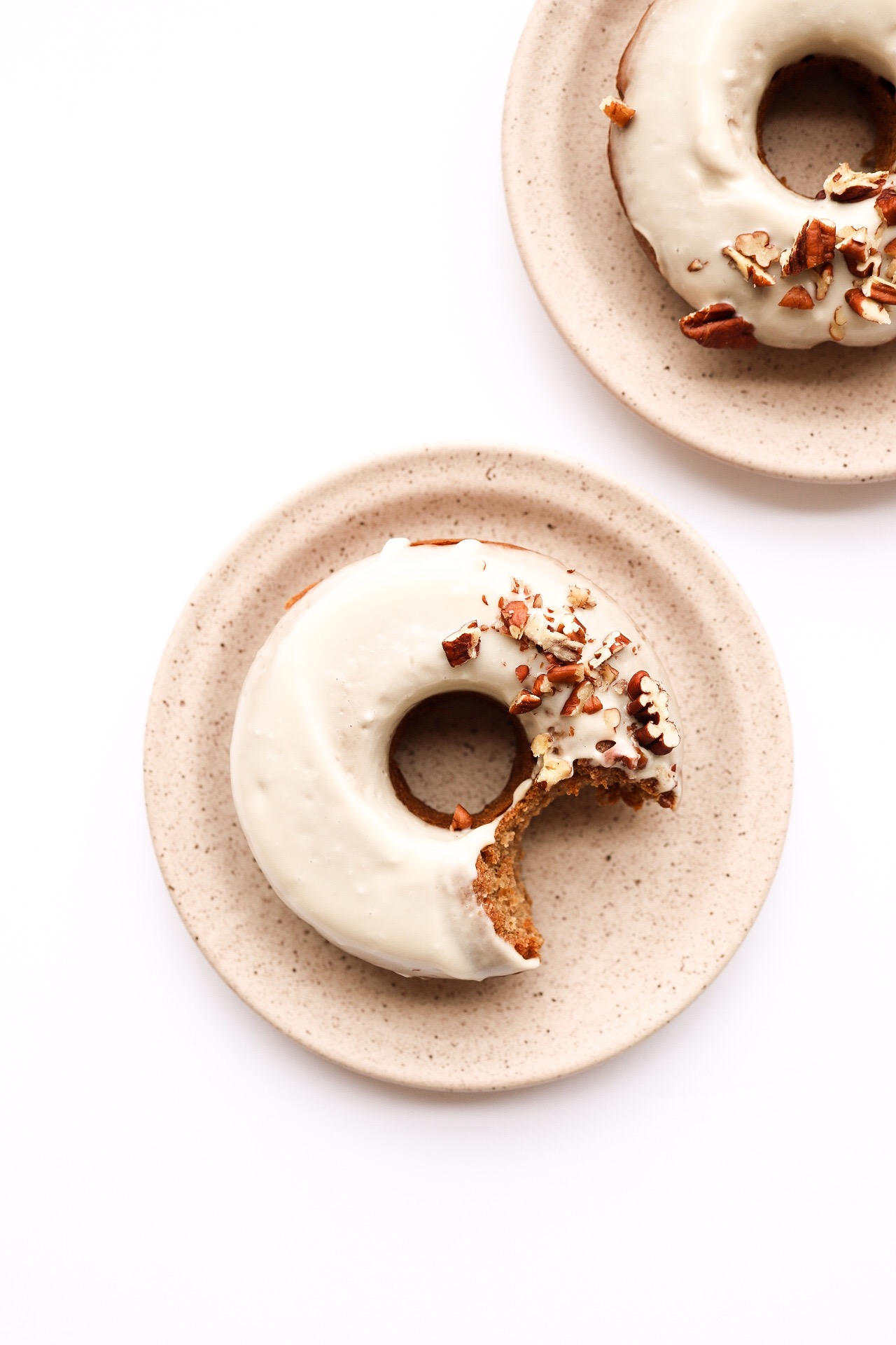 Cinnamon Spiced Doughnuts - INGREDIENTS:1 cup all purpose flour1 tsp baking powder1 tsp baking soda1/2 tsp salt1 tsp cinnamon1/4 tsp nutmeg1/3 cup apple sauce1/3 cup maple syrup1/4 cup water1 Tbsp oil1 1/2 Tbsp apple cider vinegarGLAZE:8 oz vegan cream cheese3 Tbsp maple syrup1/4 cup plant milkINSTRUCTIONS:Preheat your oven to 350F. In a medium bowl, whisk together the flour + baking soda + baking powder + salt + spices and set aside. In another bowl, mix together the remaining ingredients. Add your wet mixture to your dry and mix until everything if fully incorporated - but don't over-mix! Fill your six - doughnut pan with the batter, and bake for 15 minutes. While the doughnuts are baking, mix together the ingredients for the cream cheese glaze. When you take the doughnuts out of the oven, give them a moment to cool before dipping into the glaze. I sprinkles mine with pecans, and I highly recommend you do the same!