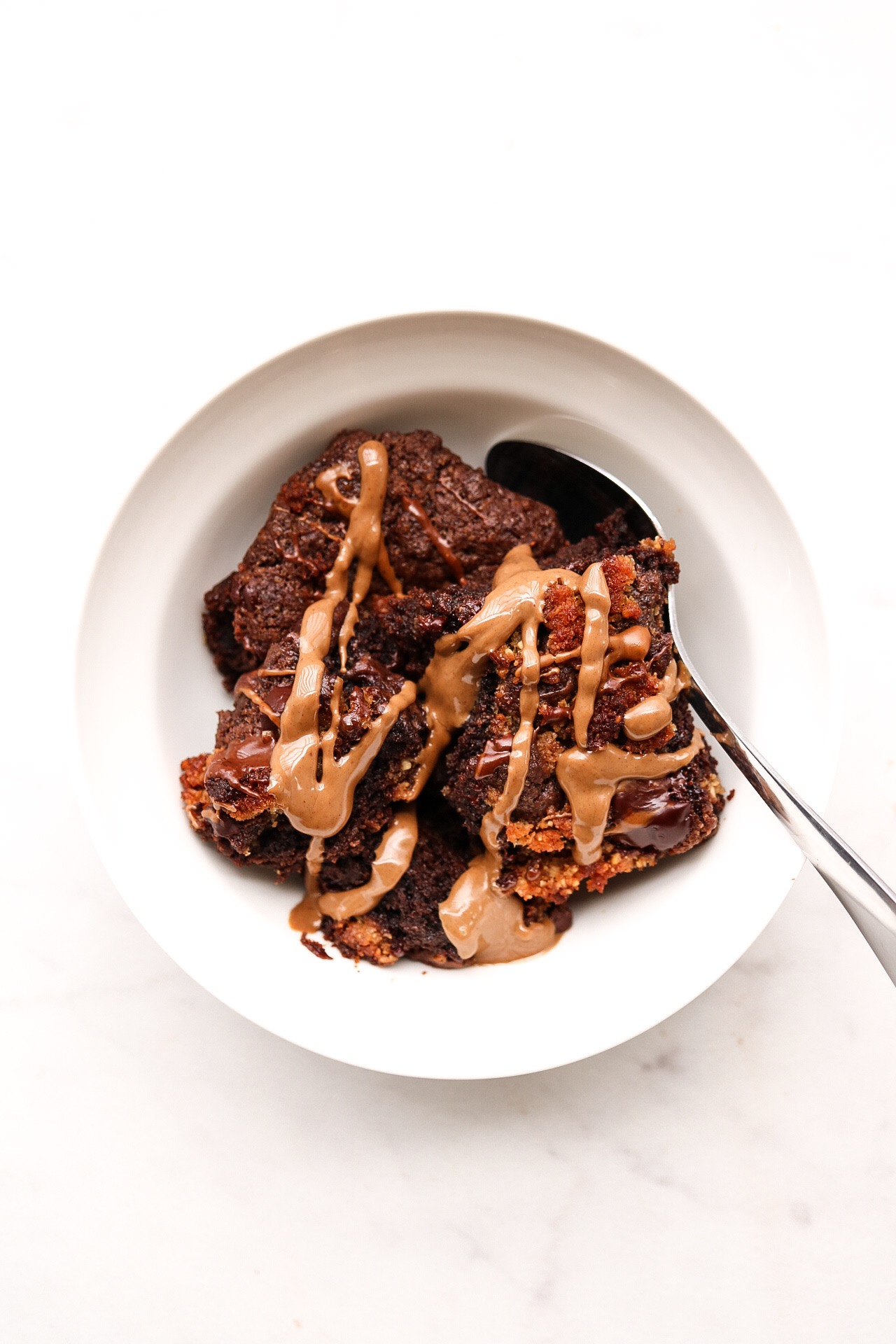 Salted Caramel Chocolate Brownies - INGREDIENTS:1 cup all purpose flour1/4 cup cacao powder1/2 tsp baking soda1 tsp salt1 flax egg1/3 cup melted coconut oil2/3 cup brown sugar3 Tbsp nut butter1 tsp apple cider vinegar1/4 cup warm water1 bag Sejoyia salted caramel coco-roons1/3 cup chopped chocolateINSTRUCTIONS:Preheat your oven to 350F. Line an 8x8 baking pan with parchment paper and set aside. In a medium bowl, whisk together the flour, cacao powder, baking soda, salt, sugar, and set aside. In another bowl, combine your flax egg, melted coconut oil, nut butter, vinegar, and warm water. Add the wet mixture to the dry and combine. Then, fold in your chopped chocolate, as well as half of the coco-roons. I just crumbled the coco-roons with my hands before folding in, but you can do it however you prefer. They're soft anyway, so they'll break easily when you're mixing. Put the batter into the baking pan and spread evenly. Crumble the remaining coco-roons on top, and add some more chopped chocolate if you like. Bake the brownies for roughly 40 minutes, more or less if needed.