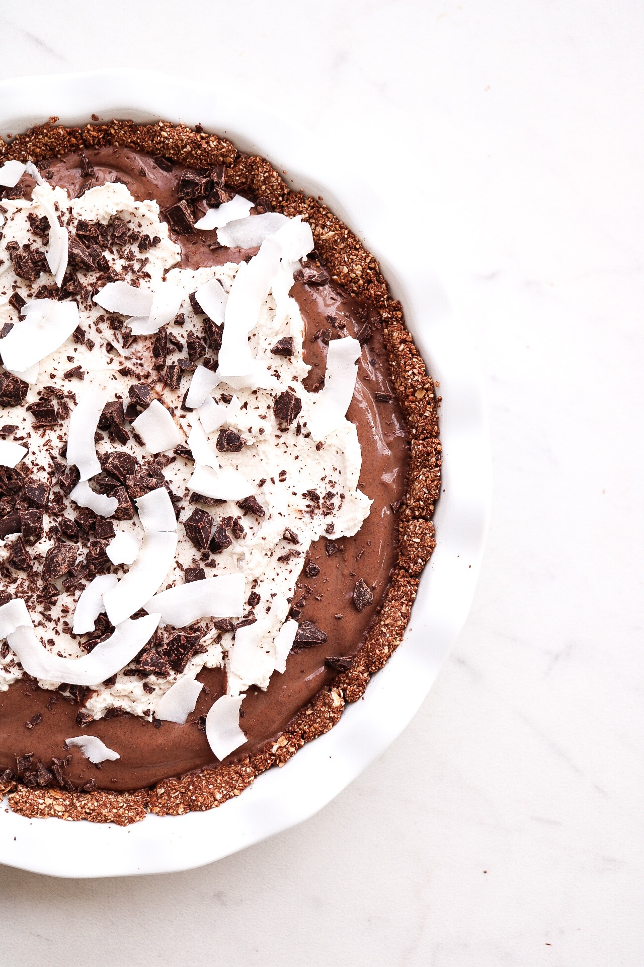Chocolate Coconut Cream Pie (v & gf) - INGREDIENTS:CRUST:1.5 cups oats1/4 cup cacao powder1/2 tsp salt4 Tbsp maple syrup4 Tbsp melted coconut oilFILLING:1 package (16 oz) silken tofu1/4 cup cacao powder1/3 cup maple syrup1/2 cup melted dark chocolate1/2 ripe avocadoCOCONUT WHIP:1 can chilled coconut cream1 5.3 oz cup vegan vanilla yogurt1-2 Tbsp maple syrupINSTRUCTIONS:For the crust, preheat the oven to 350F. In a food processor, blend your oats into a flour. In a bowl, combine all of the remaining crust ingredients until a dough has formed - form the crust into your pie pan, and bake for about 20 minutes. While the crust is baking, in a blender combine your filling ingredients. Get rid of excess water with the silken tofu the best you can before placing into the blender. Make sure your crust has cooled before adding in the pudding filling. As for the coconut whipped cream, whip together your coconut cream, yogurt, and maple syrup until you get the desired consistency. Decorate the pie as you wish, and place into the fridge for at least two hours up to overnight.