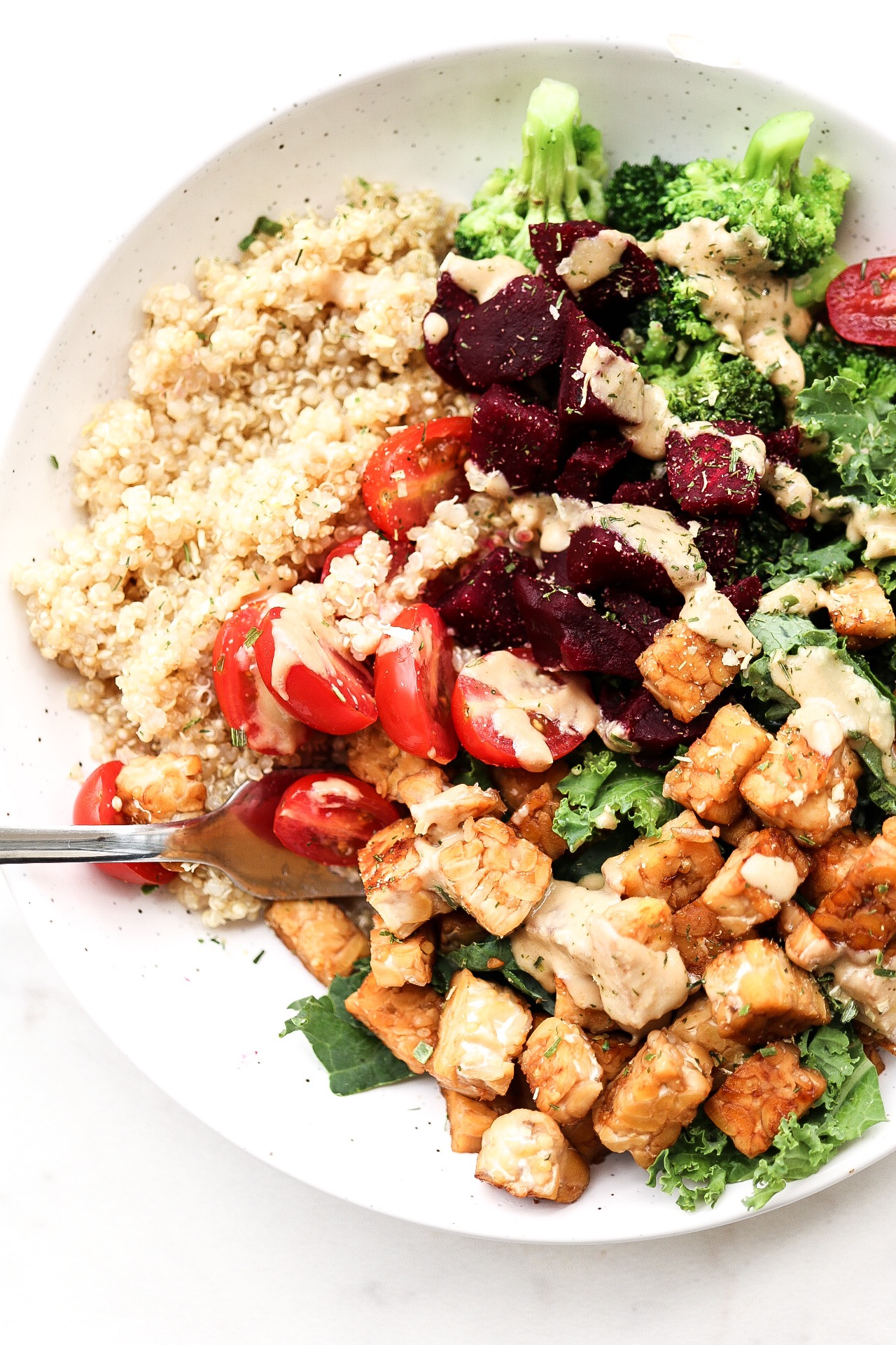 Quinoa & Beet Tempeh Bowl - INGREDIENTS:BOWL1/3 cup cooked quinoa1/4 cup cooked beets1/4 cup boiled broccoliSliced cherry tomatoesHandful of kaleTahini & dijon mustard for dressingSalt & seasonings of choiceSWEET TEMPEH1 package of tempeh - diced1/2 tsp salt1/2 cup water3 Tbsp coconut aminosINSTRUCTIONS:Meal-prep a big batch of quinoa for days ahead - or just make enough for one meal! It's up to you. Cook your beets and broccoli (I usually use frozen), slice up your tomatoes, and wash your kale. Add everything into a bowl and set aside. In a saucepan, add in your chopped tempeh as well as the water, salt, and coconut aminos. Let it simmer for about 5 minutes, until there is no longer any liquid and the tempeh is golden. Add as much tempeh to your bowl as you please - I usually use 1/3 or 1/4 per meal! As for dressing and seasoning, I just add in usually 2 Tbsp of tahini and 1 Tbsp of dijon mustard, along with a generous sprinkle of salt and other spices such as onion powder and garlic powder.