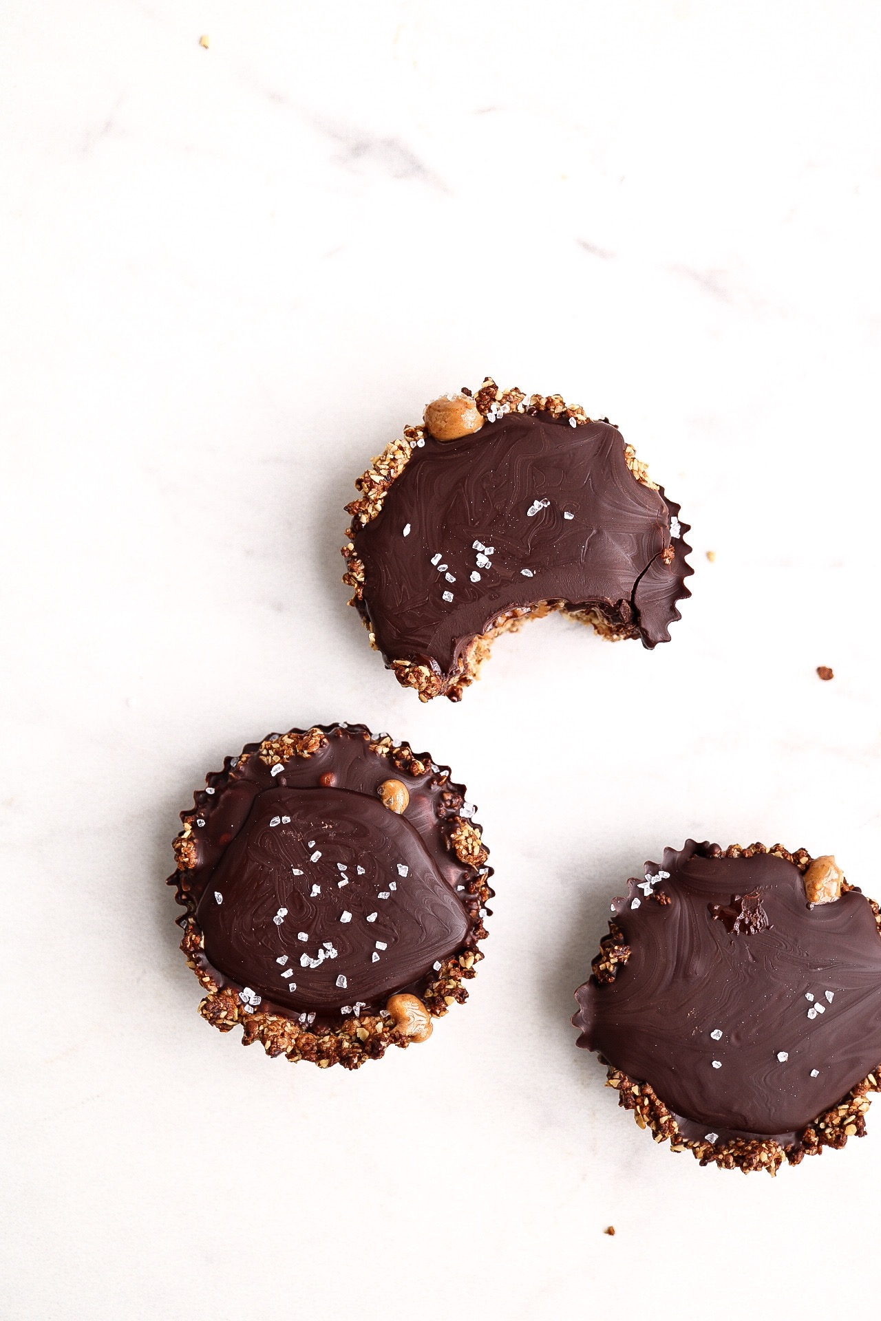 Chocolate Peanut Butter Granola Cups - INGREDIENTS:1 cup old fashioned oats1/3 cup walnuts1/2 cup raisins1/4 tsp saltSalted peanut butter1 bar Alter Eco dark chocolateINSTRUCTIONS:Preheat your oven to 350F. In a food processor, blend together the oats, walnuts, raisins, and salt. Line a 6 cup muffin tray with liners and place about 2 Tbsp of the dough into each cup. Press down and mold it into the cup, and bake at 350F for about 10 minutes. Allow the cups to cool and then place 1 Tbsp of salty peanut butter into each cup. Melt your bar of chocolate and layer it over the peanut butter layer, allowing the cups to chill in the fridge until firm. Add another layer of chocolate once the first has firmed, and allow it to harden before enjoying!