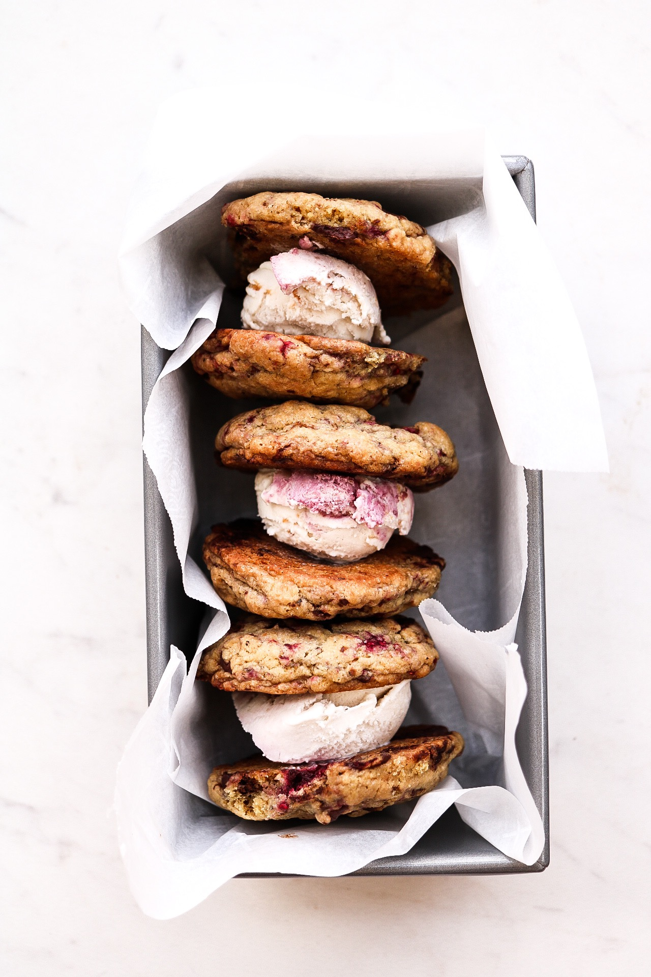 Raspberry Chocolate Chunk Ice Cream Sandwiches - INGREDIENTS:1 1/3 cup all purpose or spelt flour1/2 tsp baking powder1/4 tsp baking soda1/2 tsp salt1/3 cup melted coconut oil2/3 cup brown sugar1/4 cup warm water1/3 frozen or fresh raspberries1 bar Alter Eco 90% dark chocolate, choppedINSTRUCTIONS:Preheat your oven to 350F. Line a baking sheet with parchment paper and set aside. In a medium bowl, whisk together the flour, salt, baking soda, and baking powder. In another bowl, mix together the sugar, oil, and water. Combine the wet mixture to the dry, and fold in the chopped dark chocolate and raspberries. Scoop your cookies onto the baking sheet using a cookie scooper, or a tablespoon. Bake for about 11-12 minutes, making sure they're golden but still a bit soft. Allow the to cool before stuffing with ice cream!